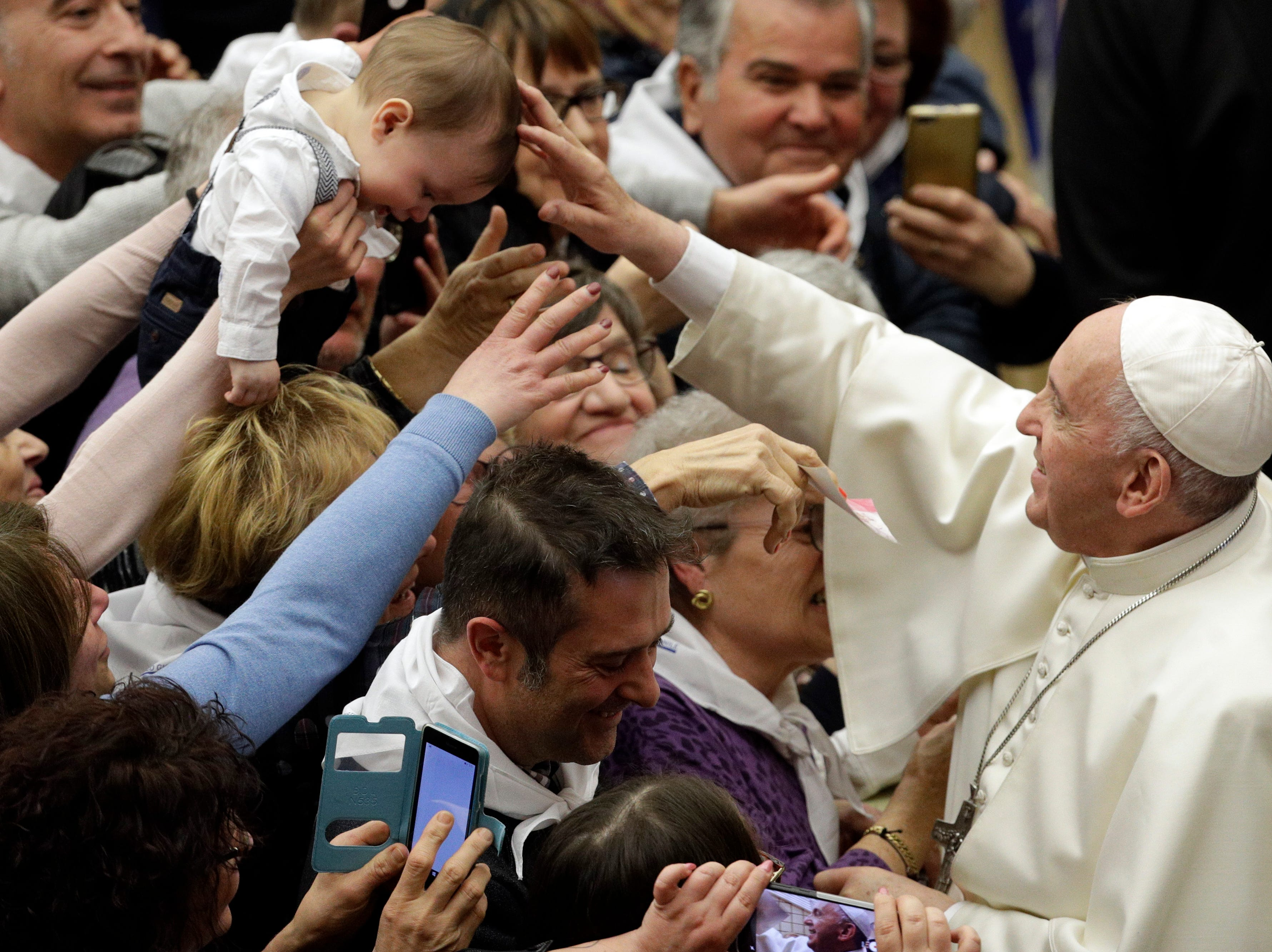 Pope Francis blesses a child on the occasion of an audience with members of youth tourism group in the Paul VI hall at the Vatican, Friday, March 22, 2019.