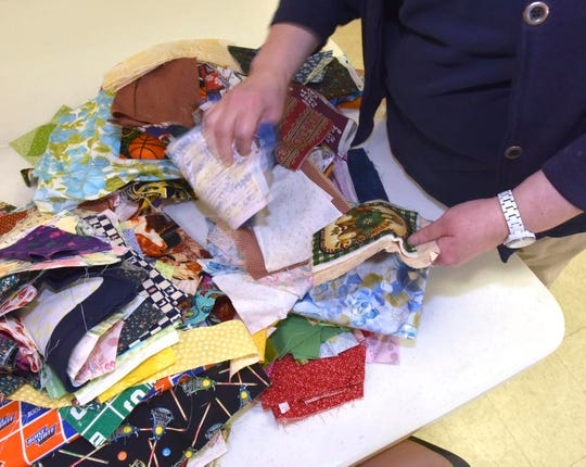 Jean Schlegelman, of Troy, sorts through pieces of fabric scraps before she uses them to make a quilt.
