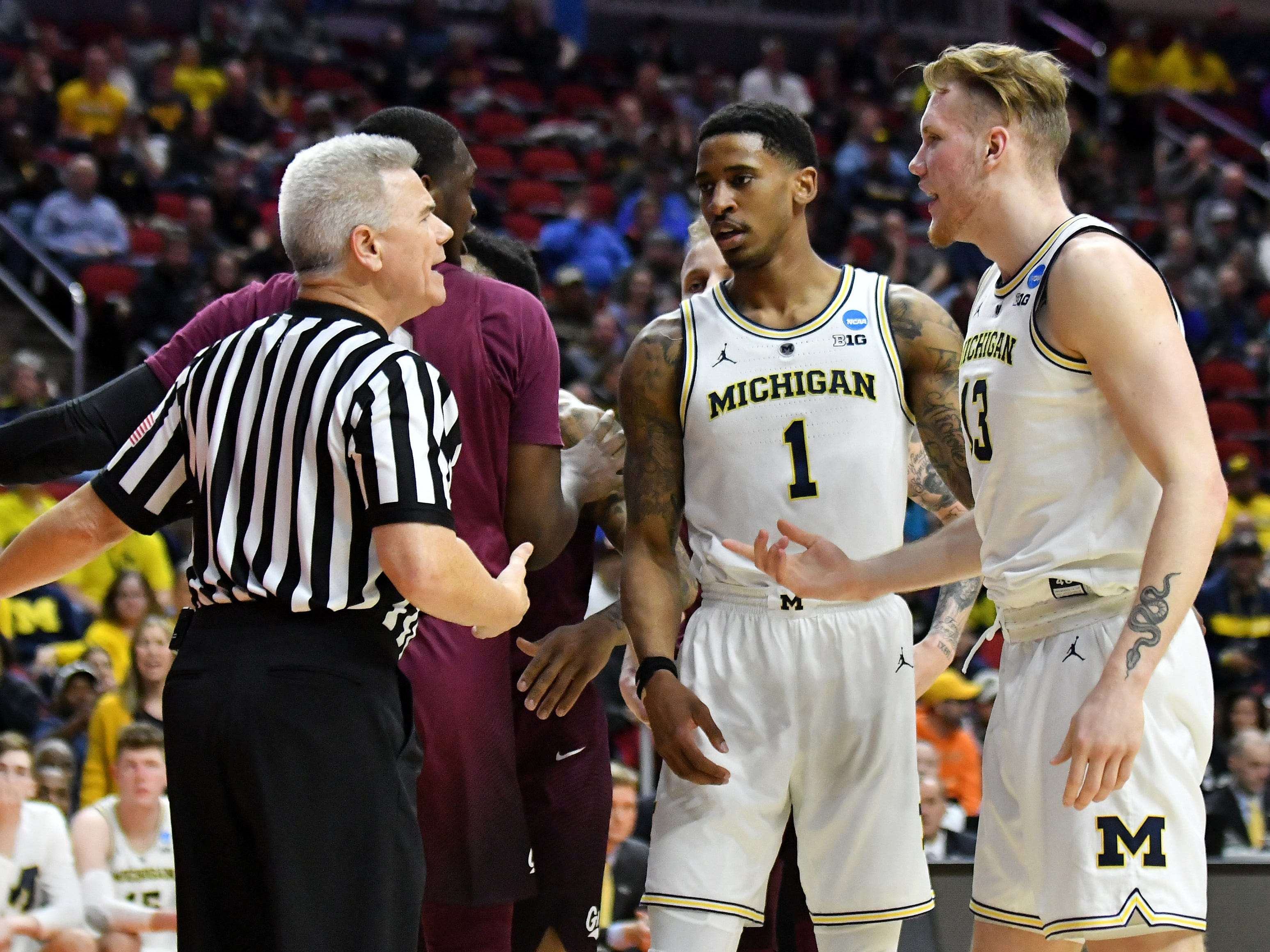 An official keeps things calm between Michigan's Charles Matthews (1)  Ignas Brazdeikis (13) and Montana players in the second half.