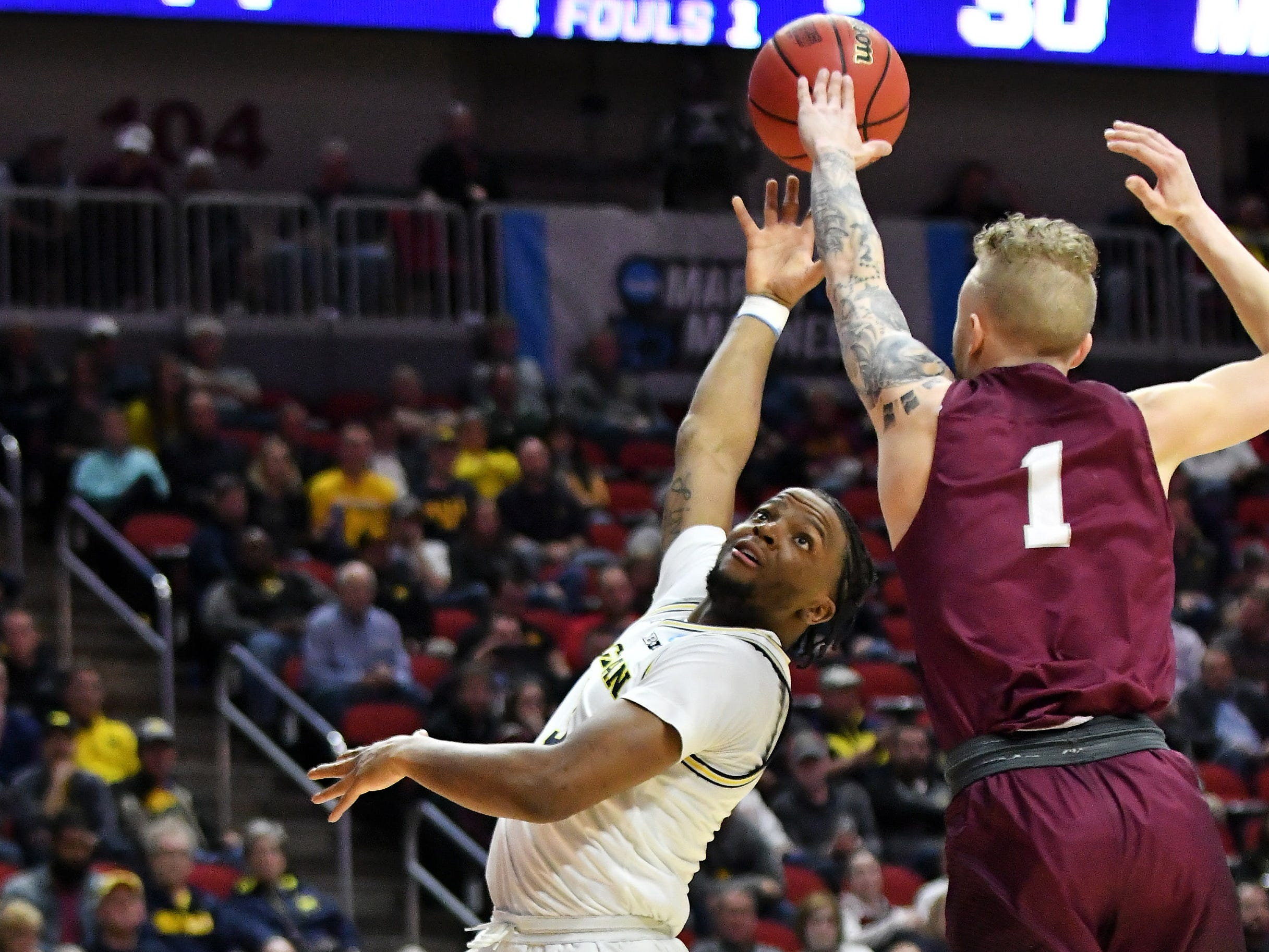 Montana guard Timmy Falls (1) defends a shot by Michigan guard Zavier Simpson (3) in the second half.