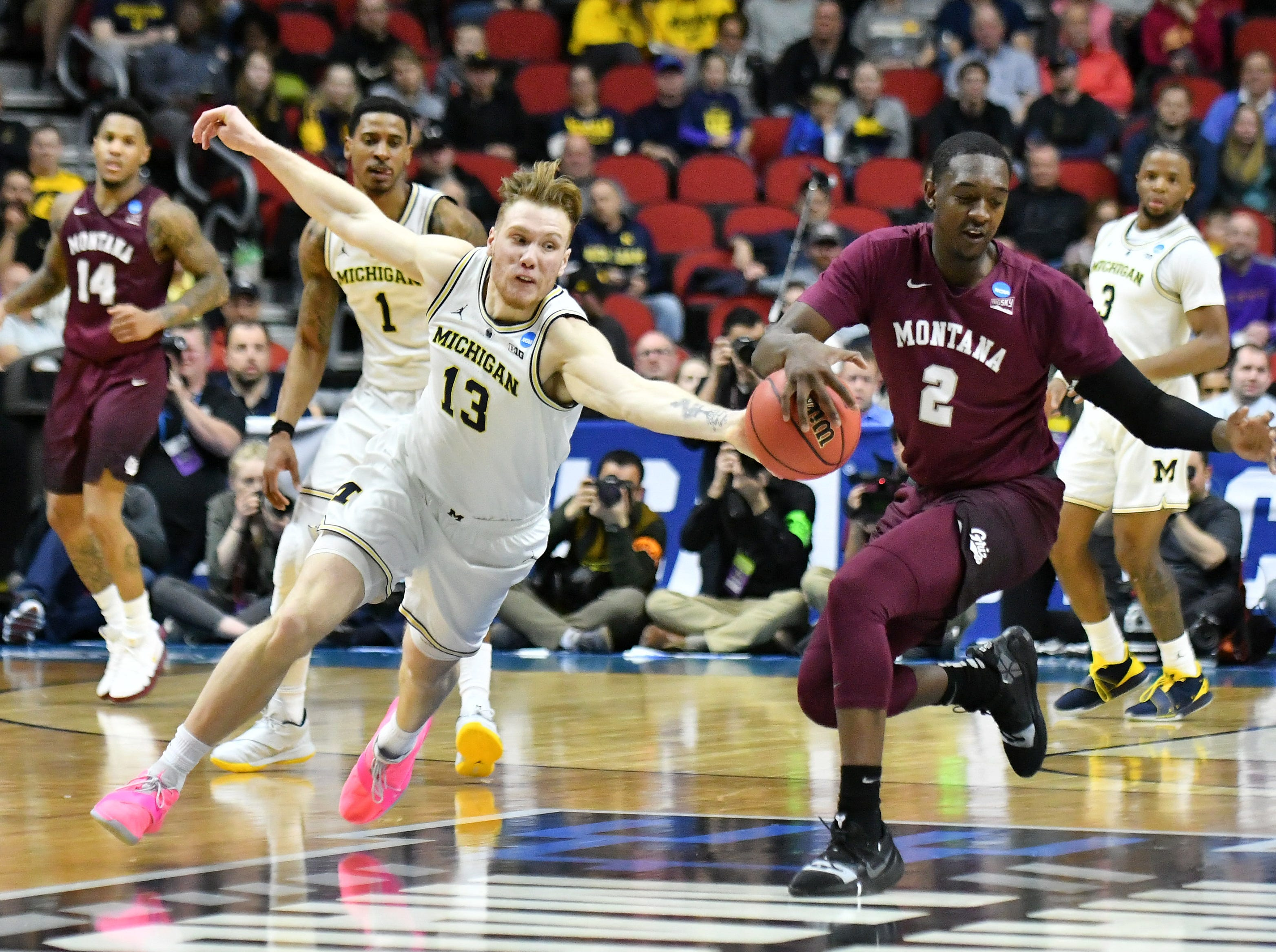 Michigan forward Ignas Brazdeikis (13) steals the ball from Montana guard Donaven Dorsey (2) in the first half.  Michigan vs Montana for Round 1 of the NCAA Tournament at Wells Fargo Arena in Des Moines, Iowa.