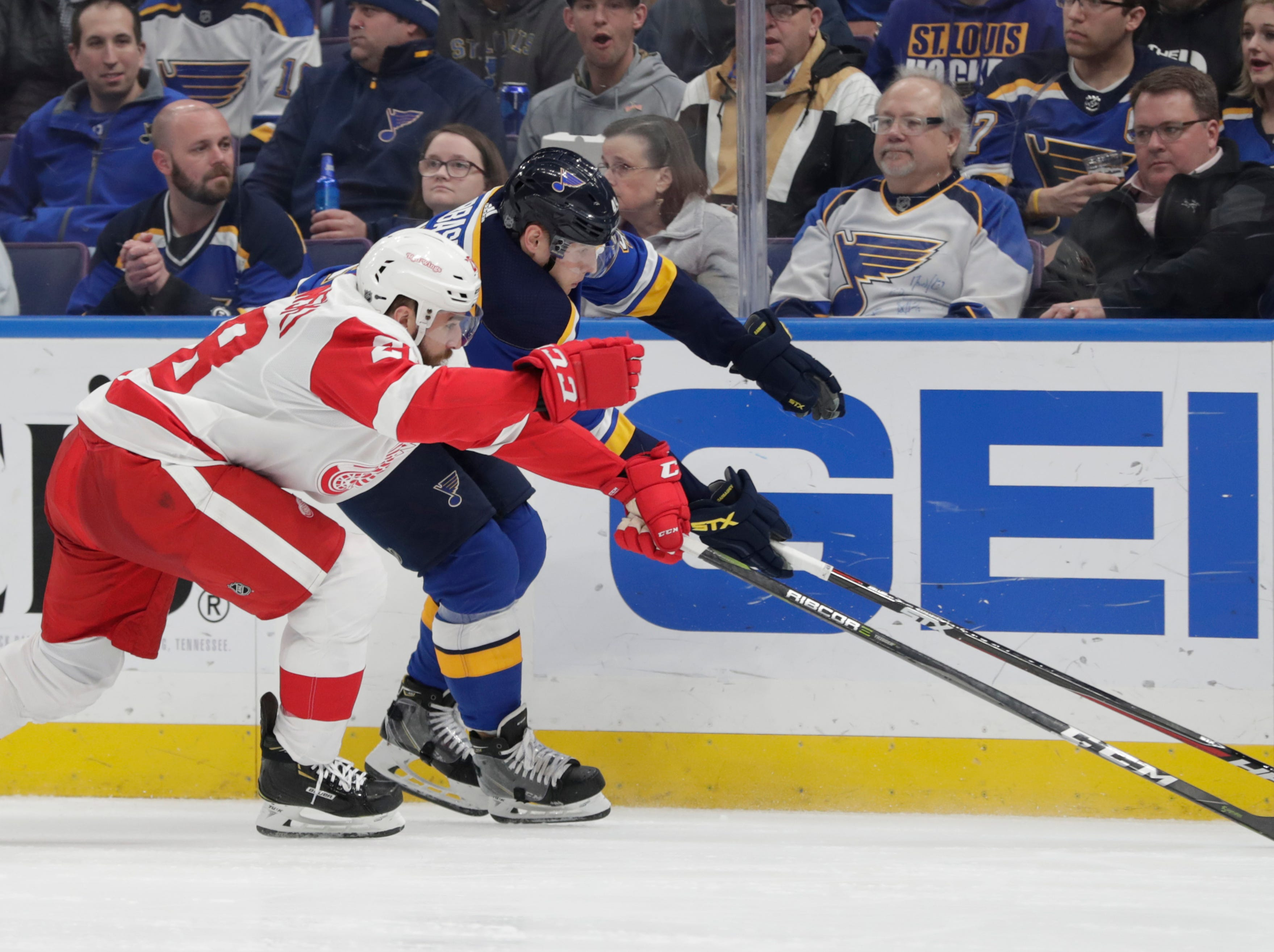 Detroit's Luke Witkowski tries to poke the puck away from St. Louis' Ivan Barbashev.