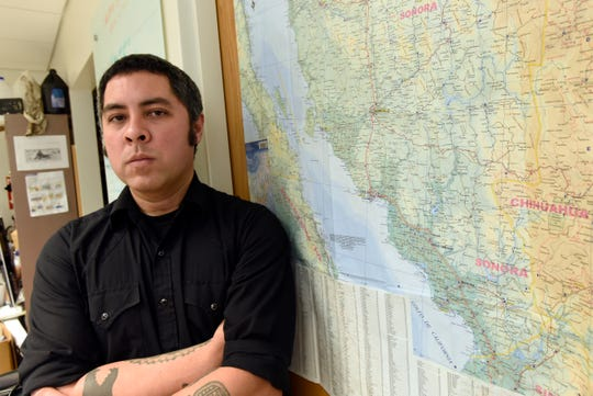 University of Michigan anthropologist Jason De Leon stands next to a map of Mexico in his office.