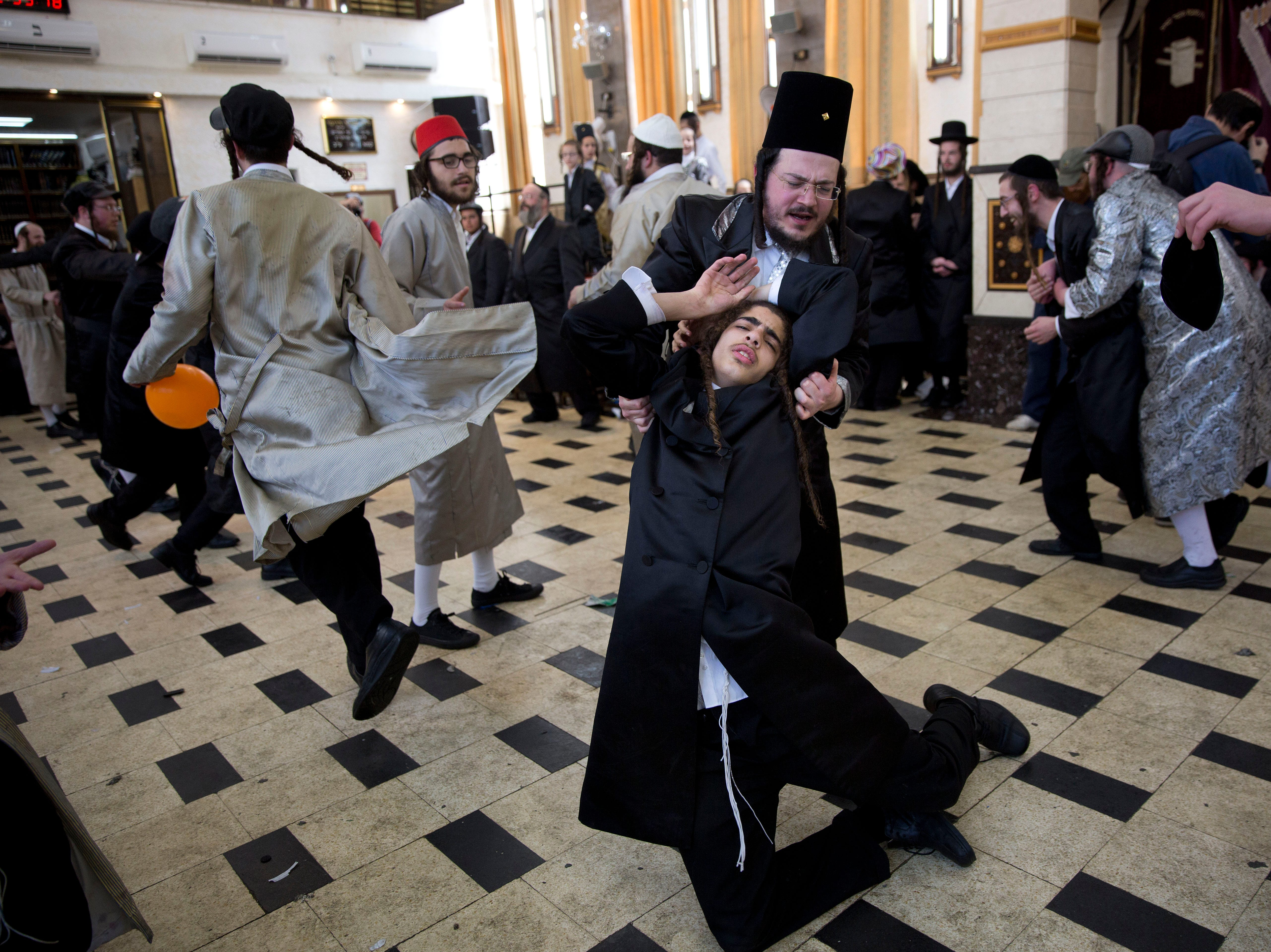 Men celebrate the Jewish holiday of Purim in the  ultra-Orthodox neighborhood of Mea Shearim, in Jerusalem, Friday, March 22, 2019. The holiday celebrates the Jews' salvation from genocide in ancient Persia, as recounted in the Scroll of Esther.