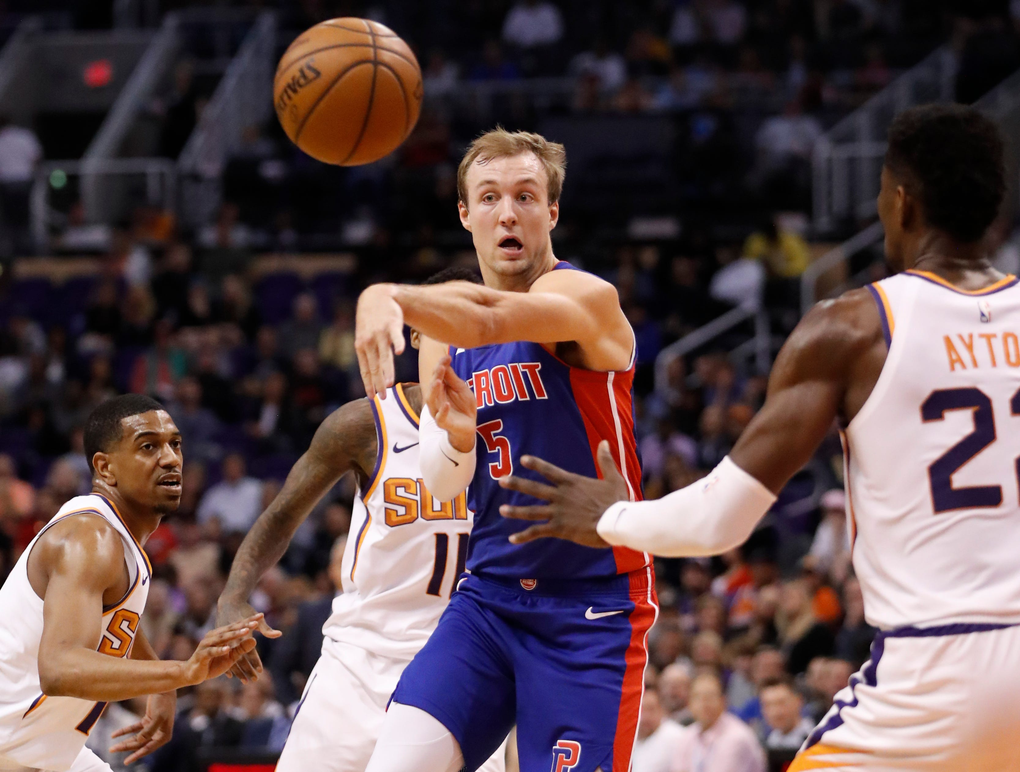 Detroit Pistons guard Luke Kennard (5) passes the ball as Phoenix Suns center Deandre Ayton (22) defends during the first half.