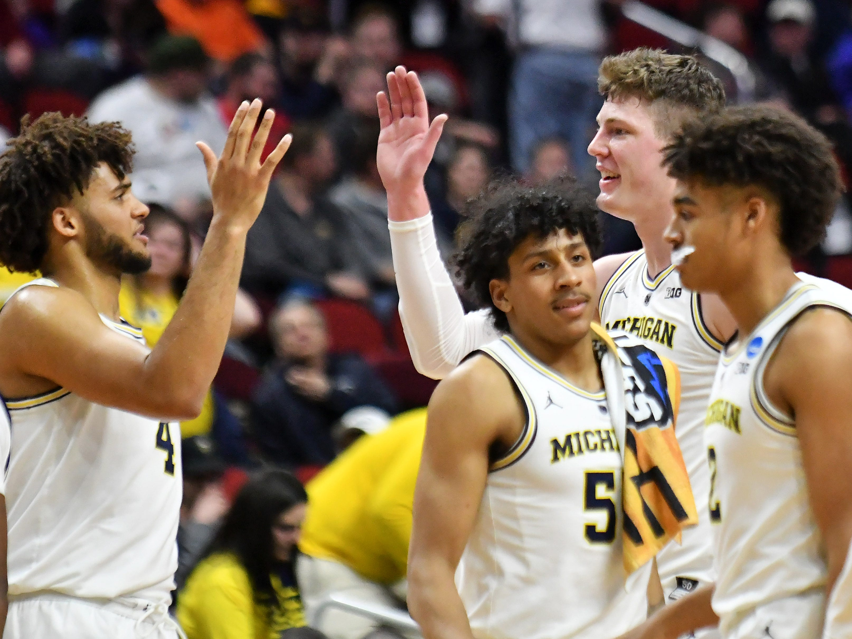 Michigan forward Isaiah Livers (4) high fives Jon Teske at a time out in the second half.