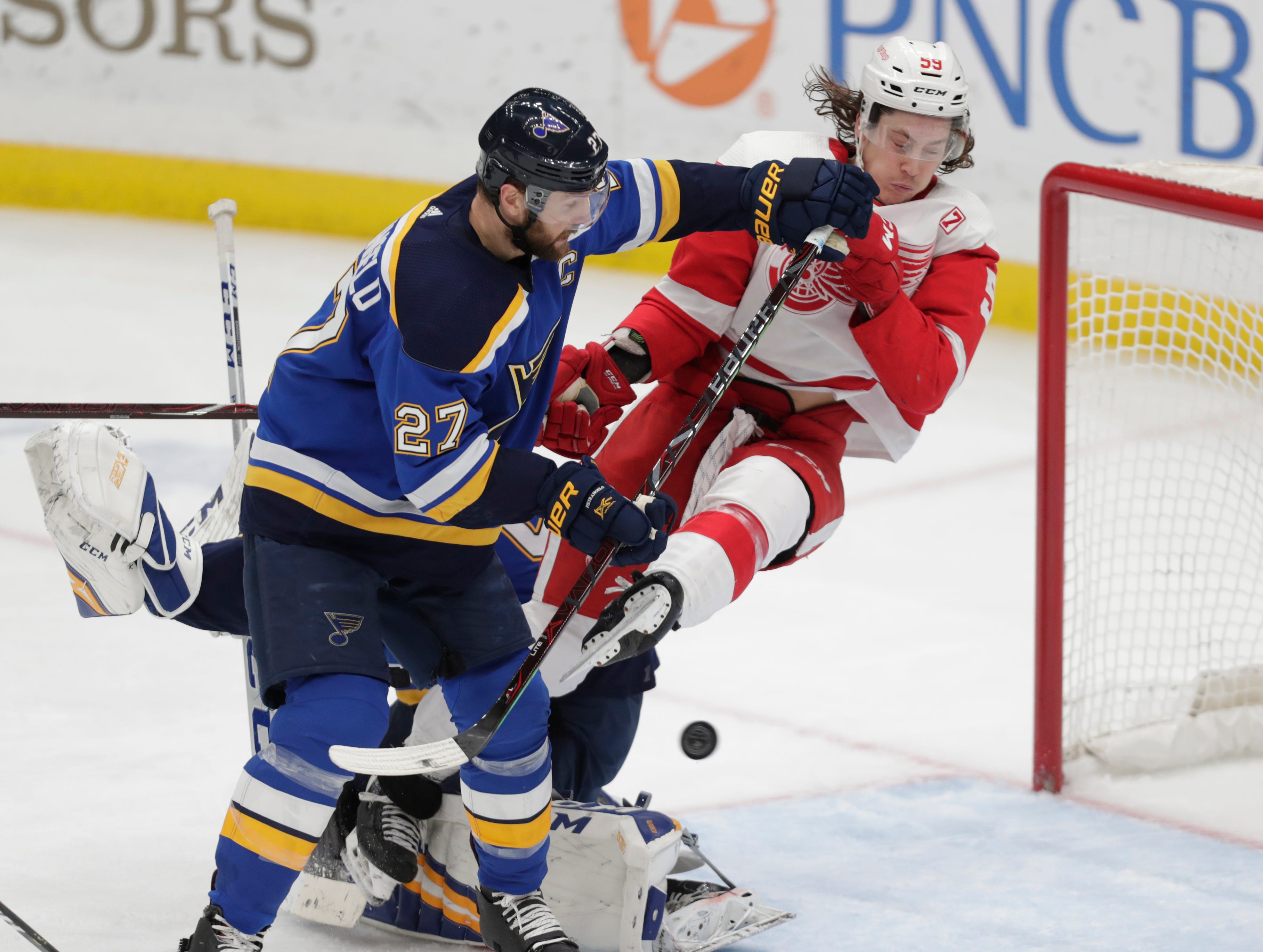 St. Louis' Alex Pietrangelo knocks Detroit's Tyler Bertuzzi off his feet as a shot from Thomas Vanek goes into the net for a goal in the third period of their game Thursday, March 21, 2019, in St. Louis. The Blues won, 5-2.