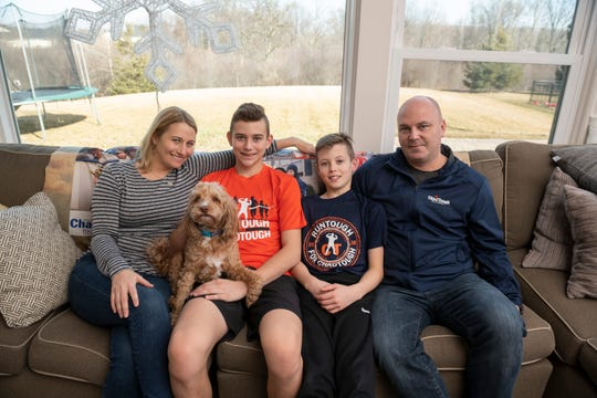 The Carr family -- Tammi, C.J., Tommy and Jason -- pose for a photo with their dog Tootie in their home in Ann Arbor on March 13.