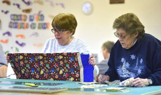 Cameo Quilter Guild president Sharon Cratsenburg, left, of Romeo, and Barbara Eaken, of Berkley, cut fabic.