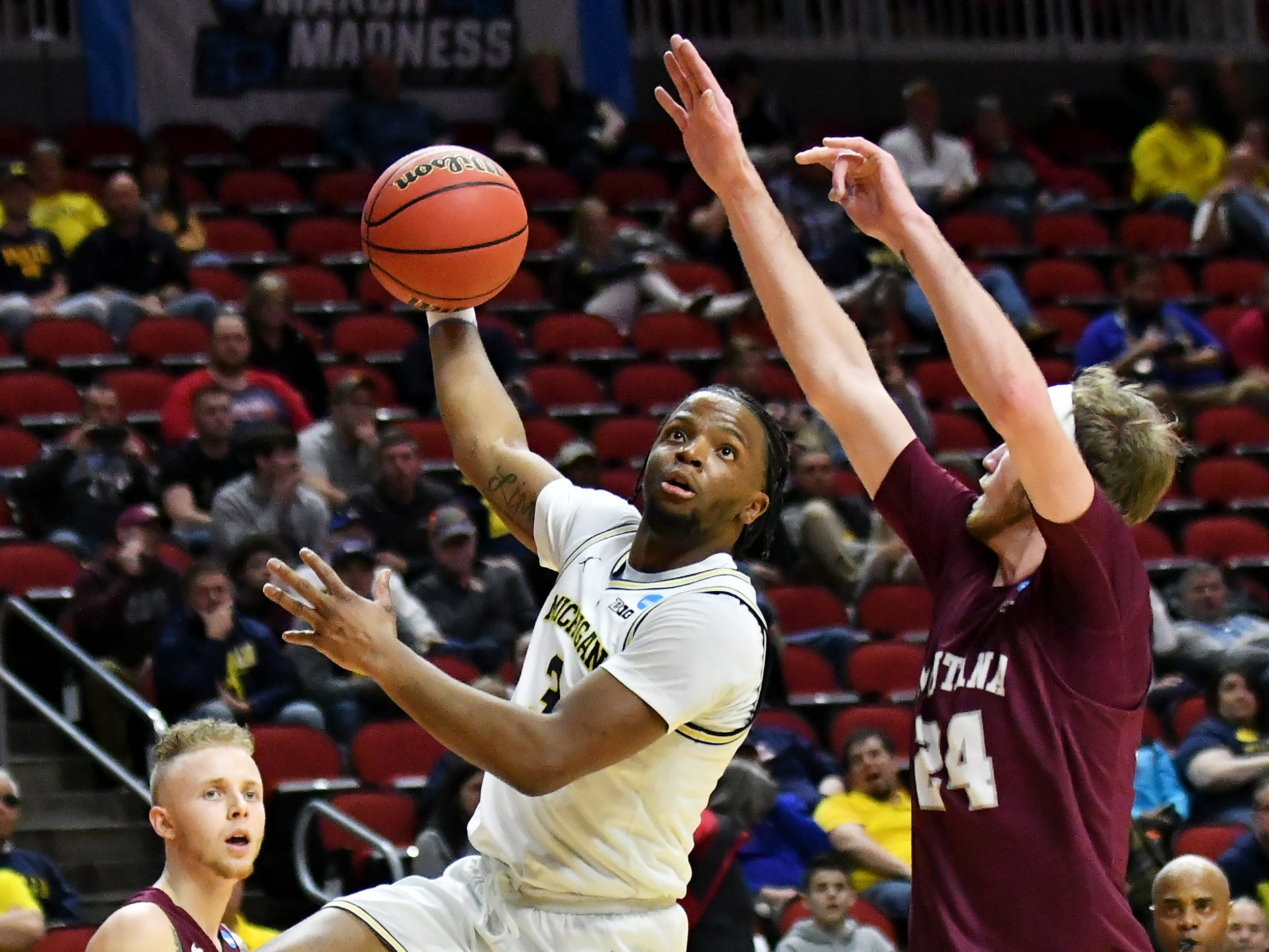 Montana guard Bobby Moorehead (24) defends a hook shot by Michigan guard Zavier Simpson (3) in the second half.