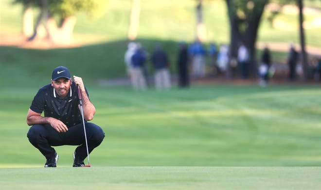 Jason Day lines up a putt on the first hole during the first round Thursday.