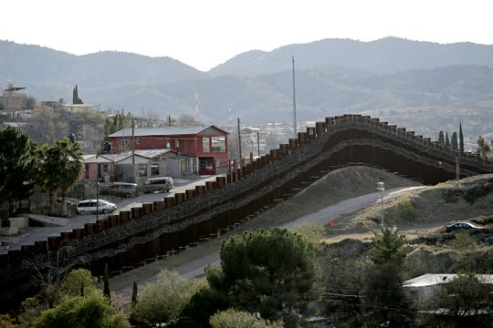 FILE - In this March 2, 2019 file photo, a razor-wire-covered border wall separates Nogalas, Mexico, at left, and Nogales, Ariz. President Donald TrumpÕs re-election campaign is urging supporters to contribute to a ÒWall Defense FundÓ as it seeks to cash in on opposition to the presidentÕs signature campaign promise.  But there is no separate fund or account to advocate for wall construction. Instead, the money goes right into the campaignÕs general coffers.