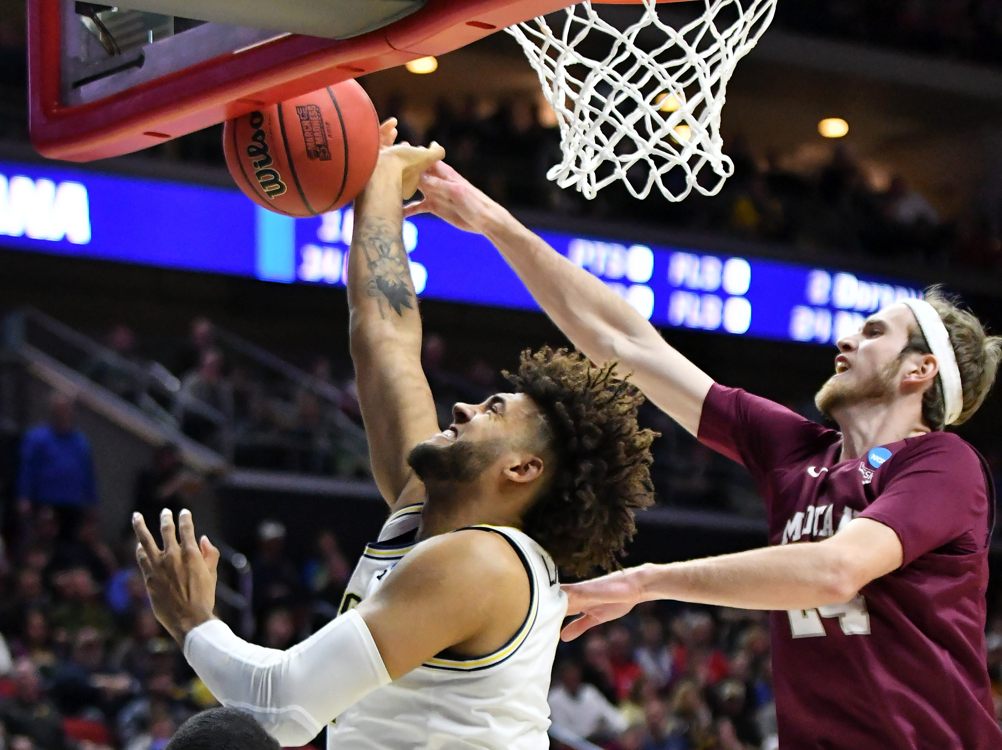 Montana guard Bobby Moorehead, right, fouls Michigan forward Isaiah Livers in the first half.  Michigan vs Montana for Round 1 of the NCAA Tournament at Wells Fargo Arena in Des Moines, Iowa.