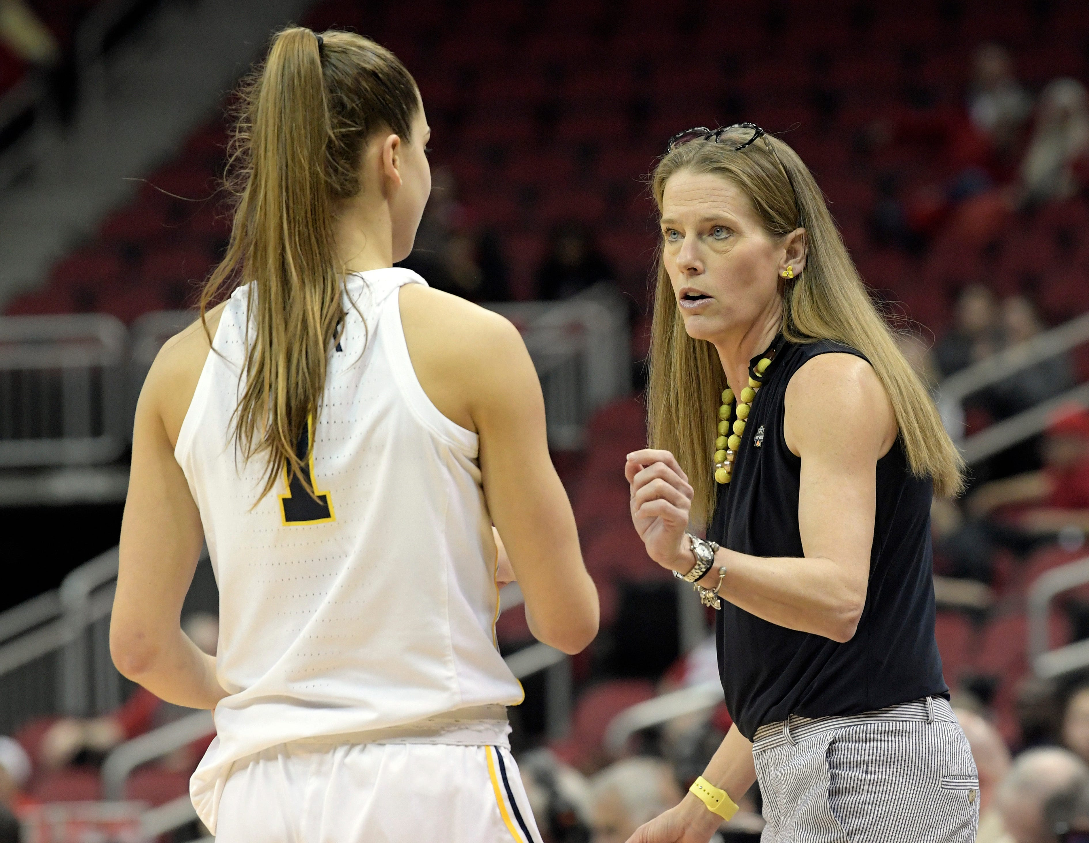 Michigan head coach Kim Barnes Arico talks with guard Amy Dilk during the second half Friday.