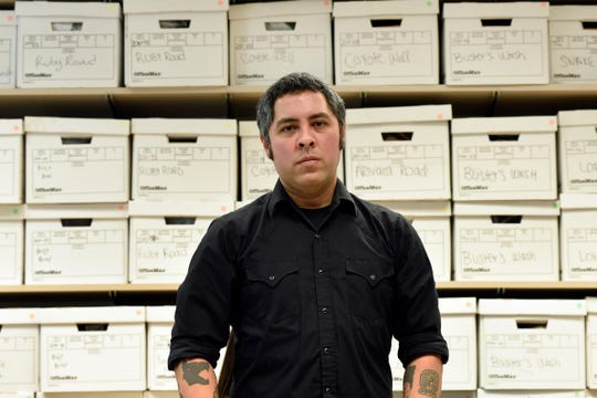 University of Michigan anthropologist Jason De León stands in his office with boxes of artifacts of things migrants left behind after crossing the Sonoran Desert.