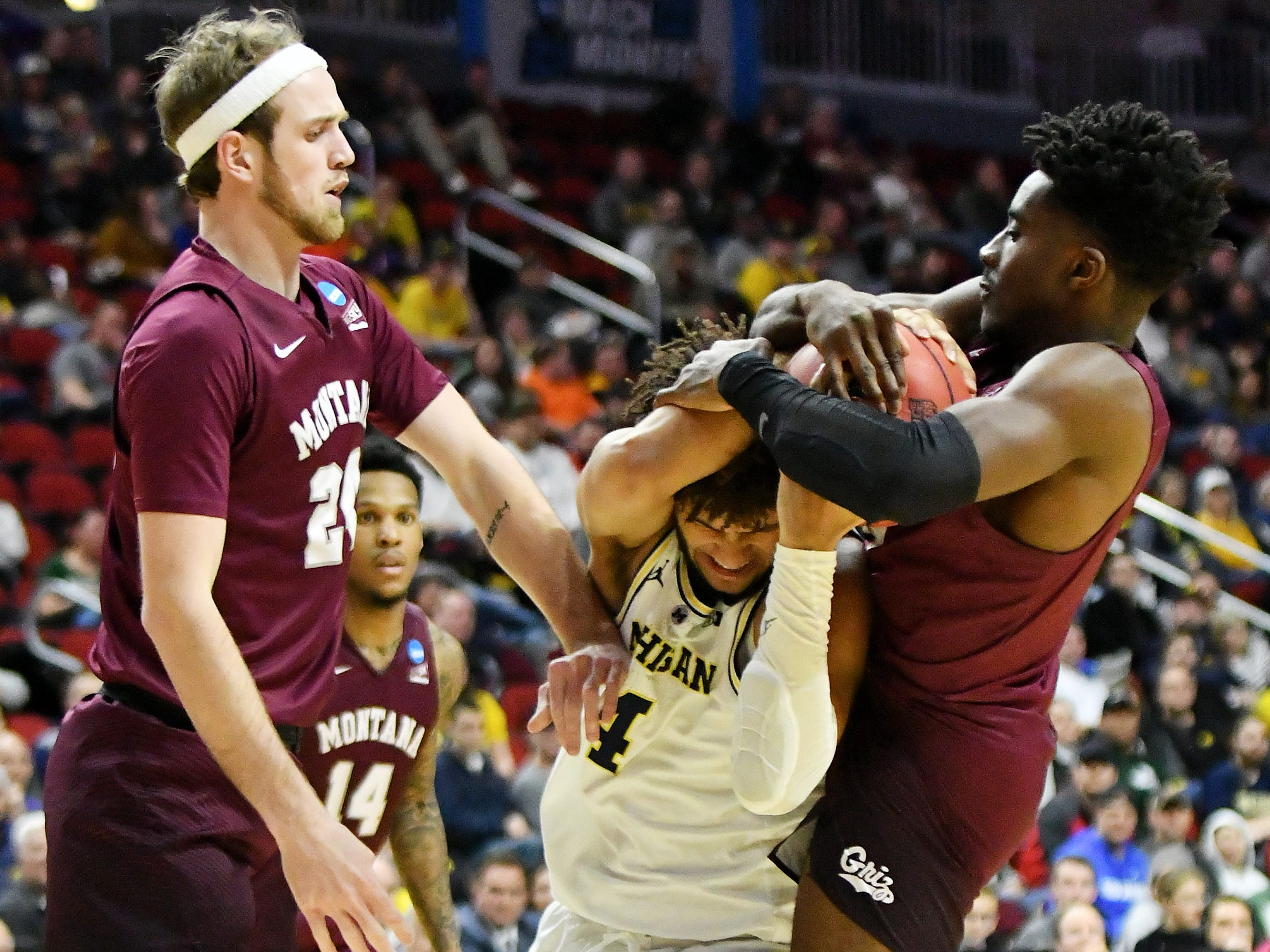 Montana guard Michael Oguine, right, tries to grab the ball from Michigan forward Isaiah Livers (4) in the second half.