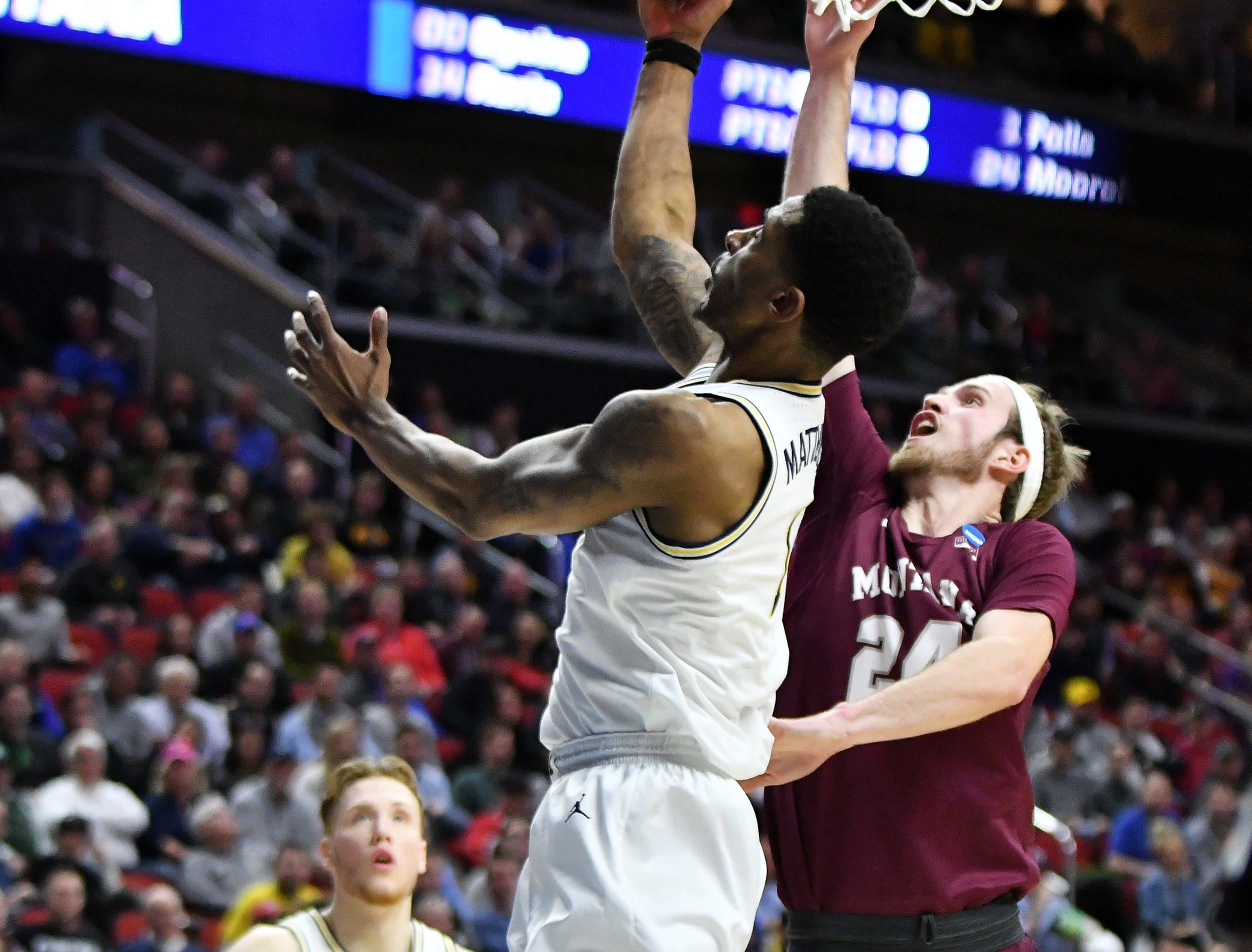 Montana guard Bobby Moorehead (24) defends a shot by Michigan guard Charles Matthews (1) in the first half.  Michigan vs Montana for Round 1 of the NCAA Tournament at Wells Fargo Arena in Des Moines, Iowa.