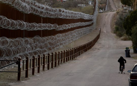 A boy rides his bike along a razor-wire-covered border wall that separates Nogales, Ariz., from Nogales, Mexico on the other side Saturday, March 2, 2019.