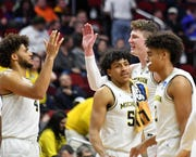 Michigan forward Isaiah Livers (4) high fives Jon Teske at a timeout in the second half Thursday.  The 2-seeded Wolverines eased past the 15-seed Montana Grizzlies 74-55.