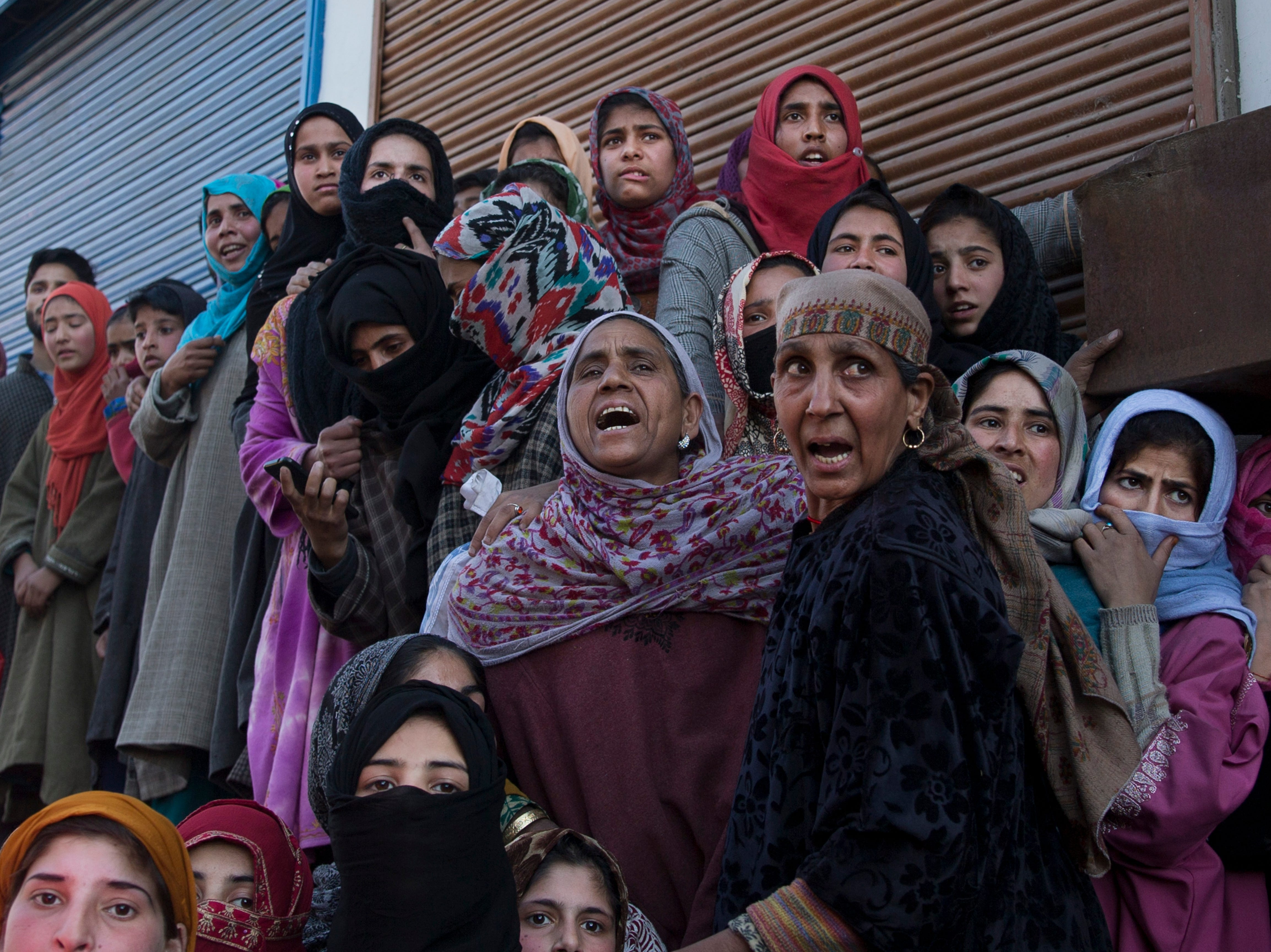 Villagers watch the funeral procession for an 11-year-old boy, Aatif Mir, in Hajin village, north of Srinagar, Indian- controlled Kashmir, Friday, March 22, 2019. Indian security forces killed five militants and the 11-year-old hostage in three separate clashes, police and the army said Friday.