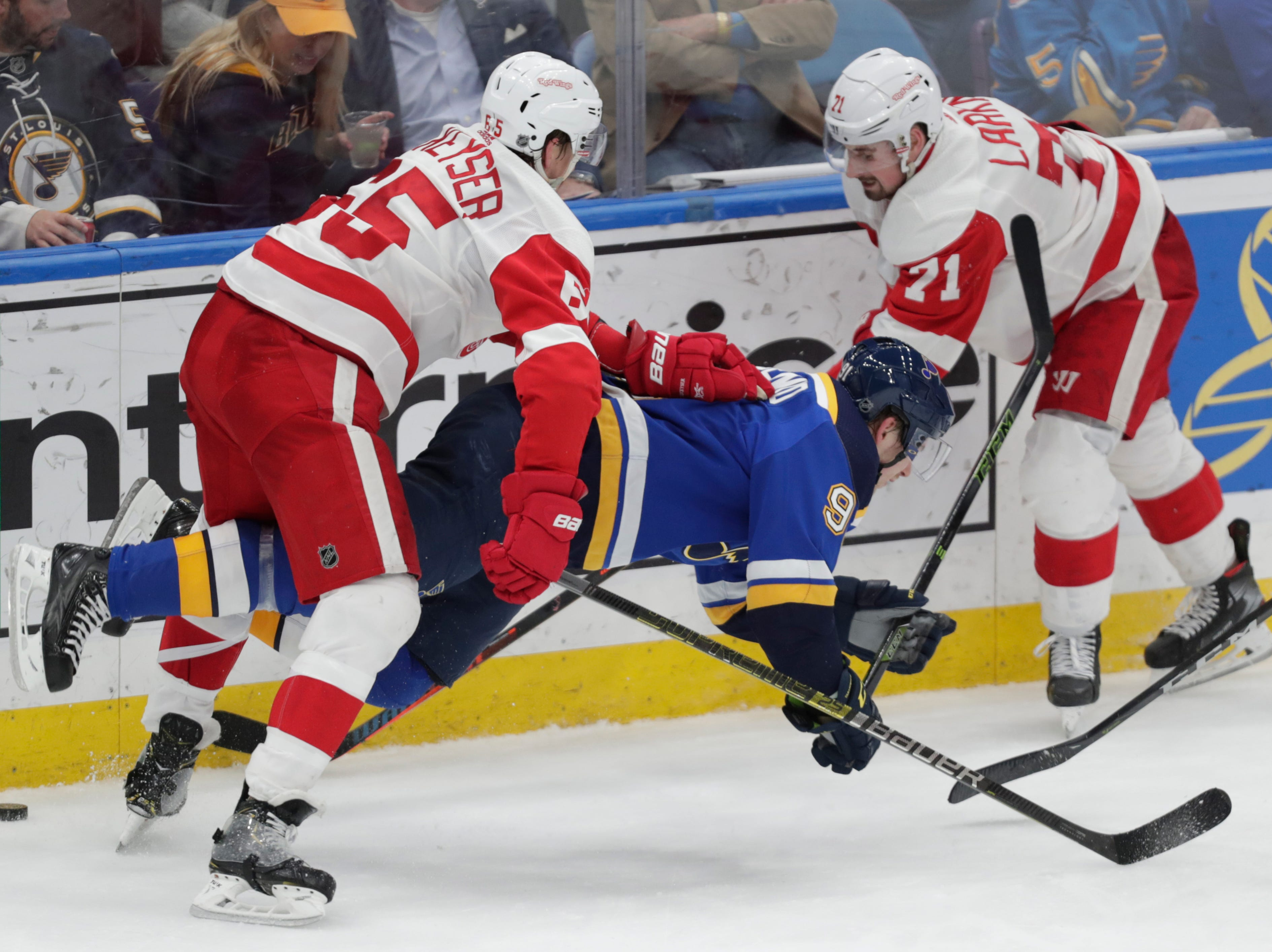 St. Louis' Vladimir Tarasenko is leveled from behind by Detroit's Danny DeKeyser (65) as Dylan Larkin reaches for the puck.