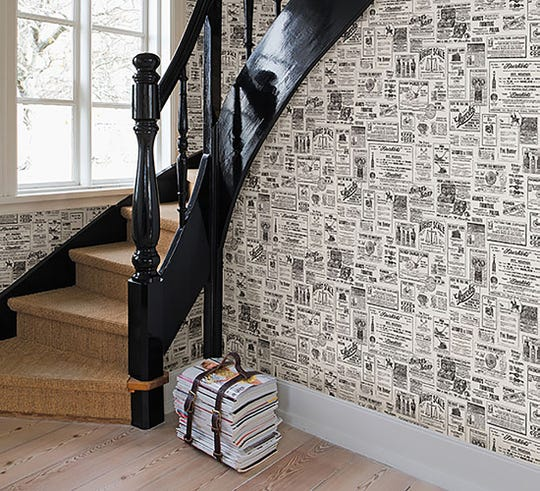 Wallpaper with a newspaper motif sets the tone in an entry.