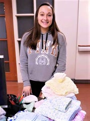 Kaitlyn DiNardo shows off some of the handmade items she donated to Guthrie's Labor, Delivery, Recovery, Postpartum department.
