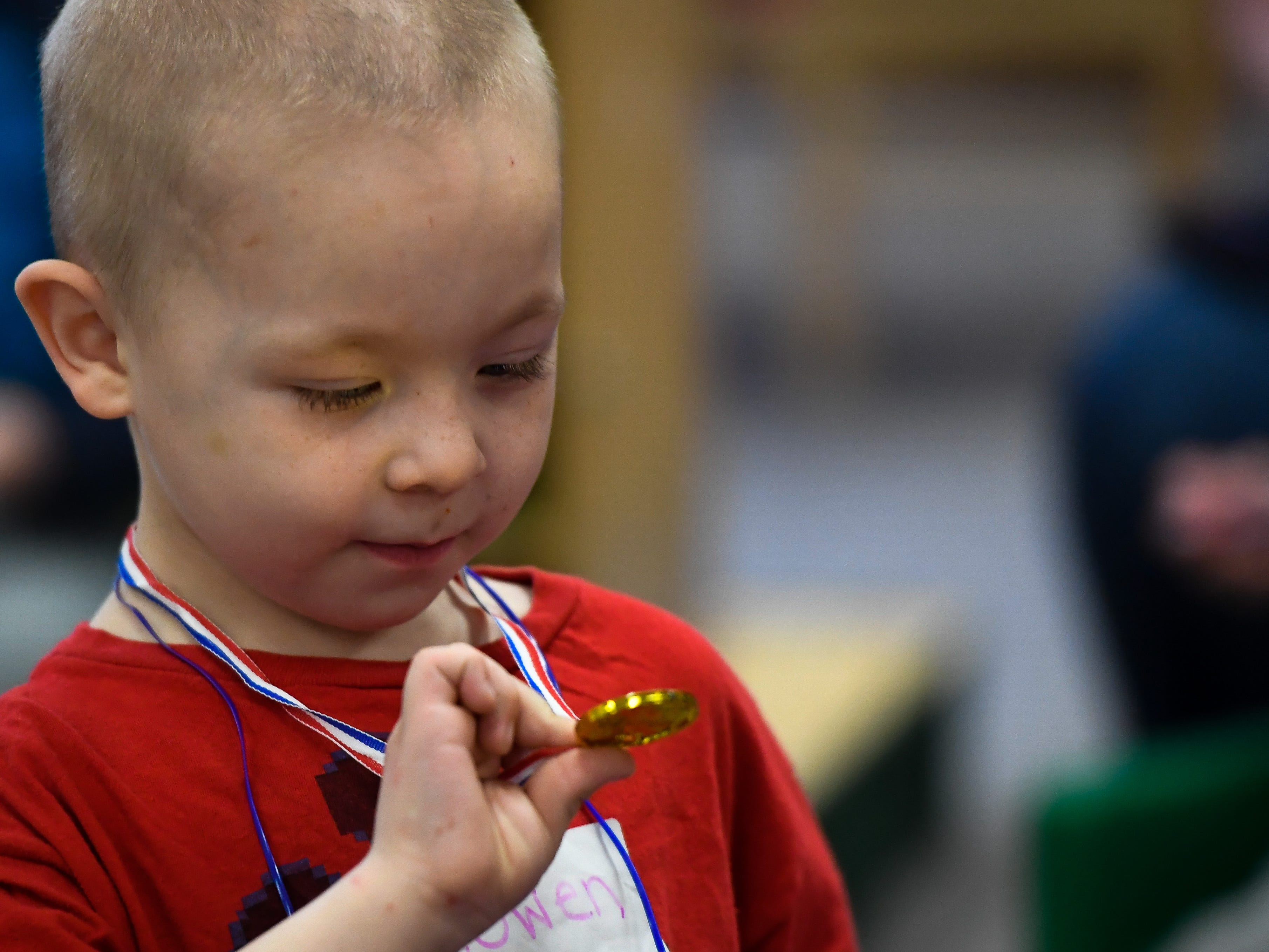 With the gold reflection on his face, Rowen Phillips, 5 years-old, checks out his medal during the Special Olympics Unified Champion School Young Athlete program at Culver Early Learning Center Friday, March 22, 2019.