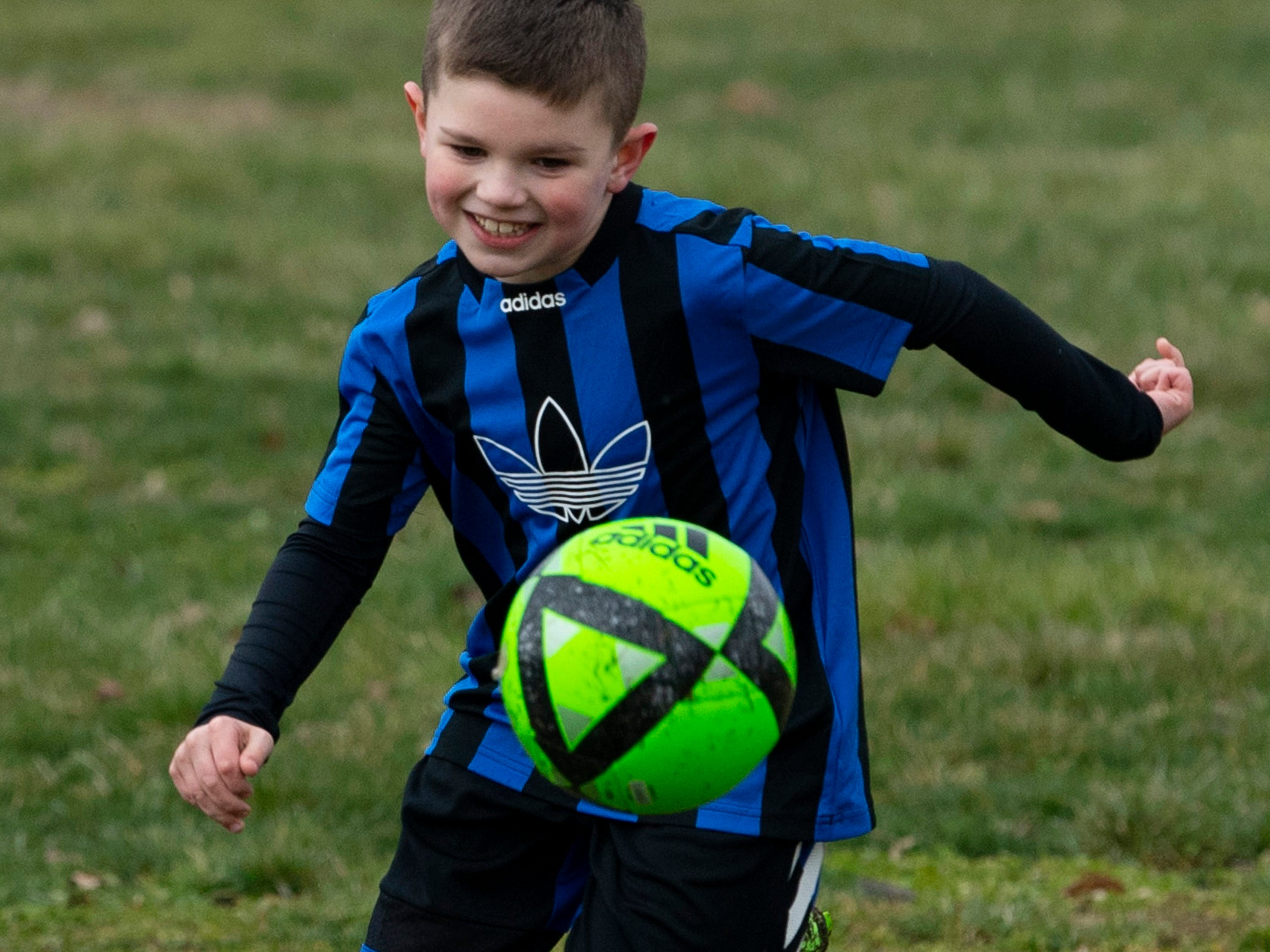 Renner Hurt, 7, of Evansville chases down a crossing pass from his dad, Brian Hurt, before his first soccer practice of the year at Vann Avenue Soccer Fields Wednesday evening.