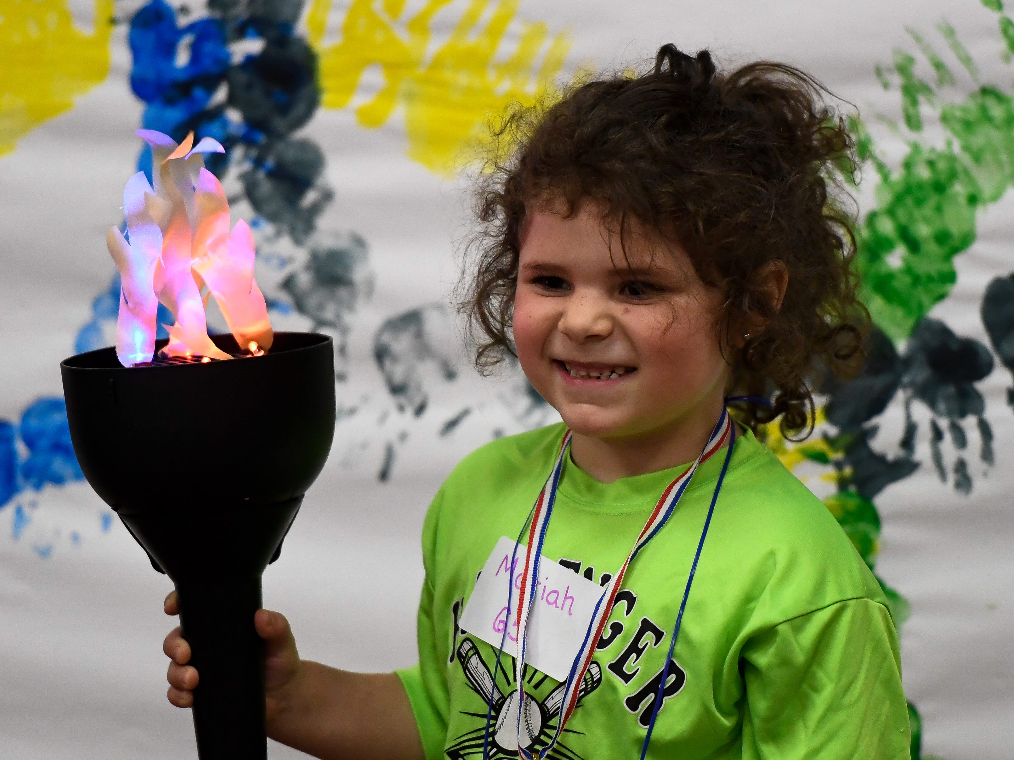 Mariah Jost, 5 years-old, on the medal stand during the Special Olympics Unified Champion School Young Athlete program at Culver Early Learning Center Friday, March 22, 2019.