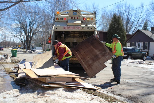 Green Bay Public Works employees Justin Madero, left, and Matt Tochterman clean up debris from a flooded basement in the 1400 block of Eliza Street Friday afternoon.