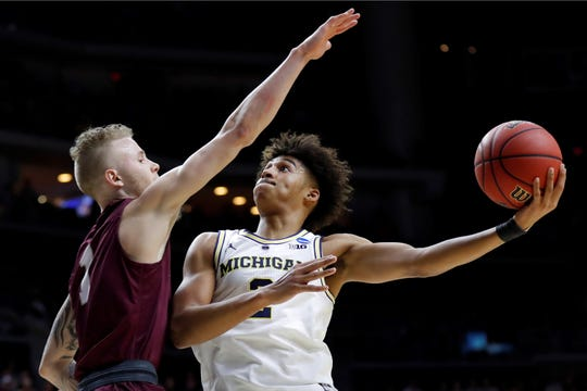Michigan guard Jordan Poole shoots over Montana guard Timmy Falls, left, during a first round men's college basketball game in the NCAA Tournament Thursday in Des Moines.(AP Photo/Charlie Neibergall)
