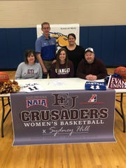Creat Falls Central's Sydney Hill, seated in center, signed her college letter-of-intent to play basketball at Evangel University in Missouri Friday. Pictured with her, from left to right, are mom Angie Hill, GFCC head coach Matthew Hauk, Sydney Hill, GFCC athletics director Jamie Stevens, and dad Shawn Hill.