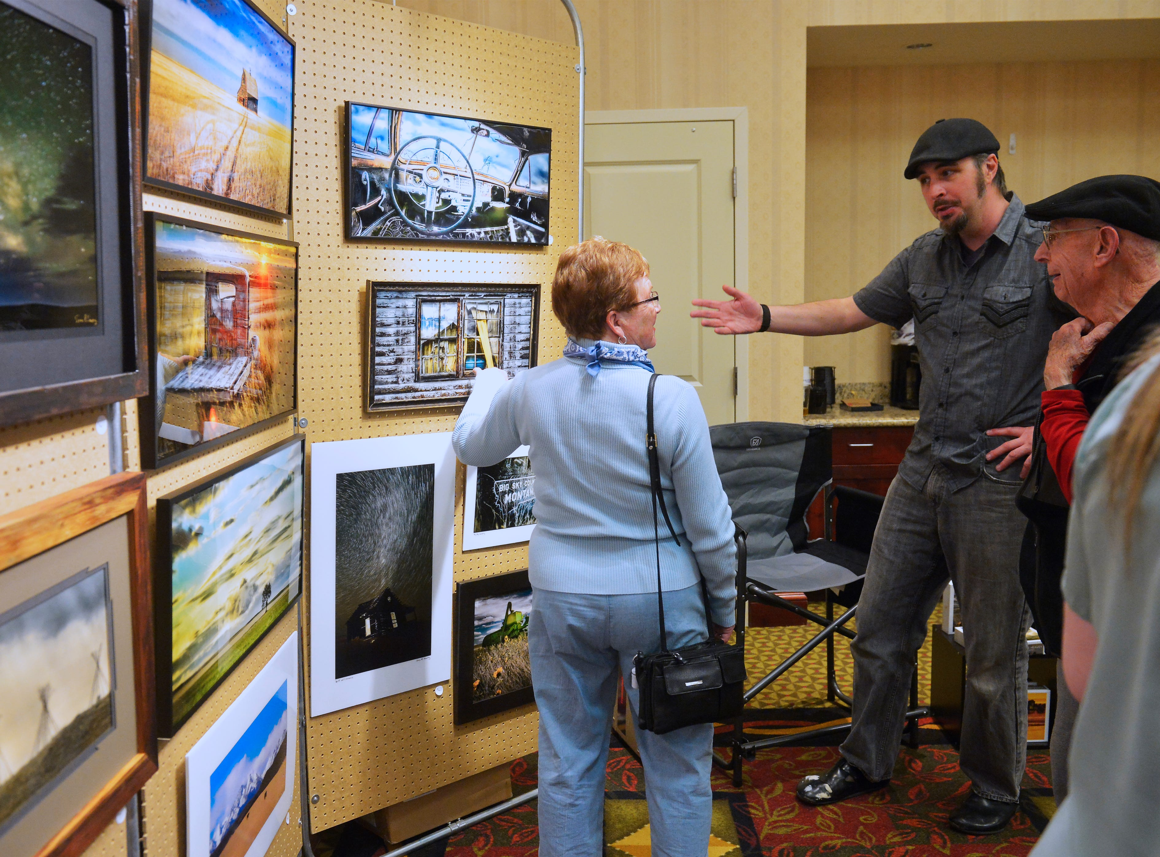 Photographer Sean Heavey talks with guests at his booth at Jay Contway and Friends Show at the Hilton Garden Inn, Thursday.