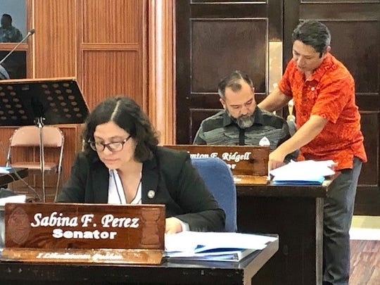 Sens. Clynt Ridgell and Wil Castro review a document during a legislative session break on Friday afternoon. Also in photo is Sen. Sabina Perez.