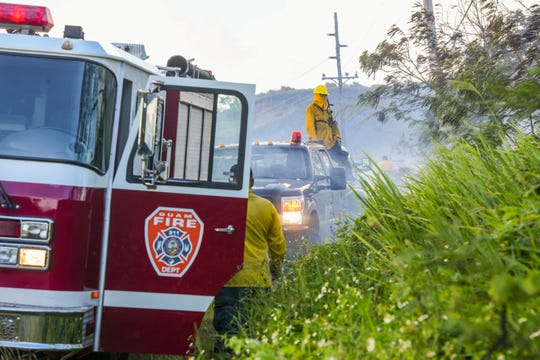 In this March 21 file photo, Guam Fire Department firefighters and Department of Agriculture forestry workers coordinate efforts as they battle a grass fire along Route 17.