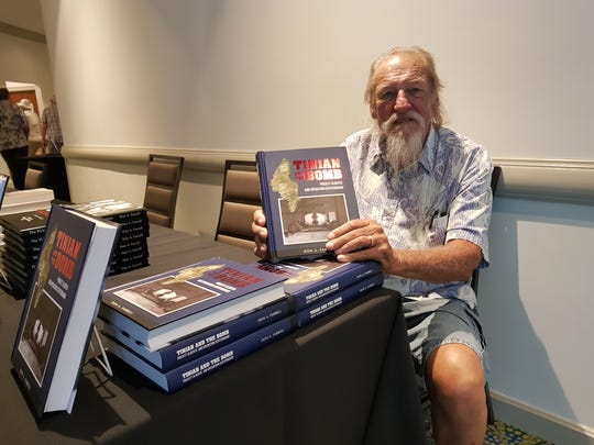 "Historian Don Farrell holds up his new book ""Tinian and the Bomb"" at the Iwo Jima Association of America Symposium at the Outrigger Guam Beach Resort."