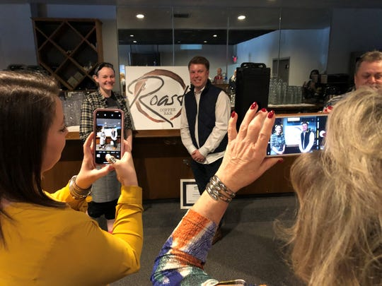asey Todd, center right, owner of Hometown Roots, and Shawna Tipton, the restaurant's kitchen manager and general manager of the soon-to-open Roast Coffee Bar, pose for photos after Hometown Roots received the Downtown Henderson Partnership's Business of the Year award on Friday.
