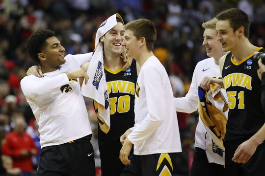 Connor McCaffery (30), Nicholas Baer (51) and the Hawkeyes react to their 79-72 win against Cincinnati.