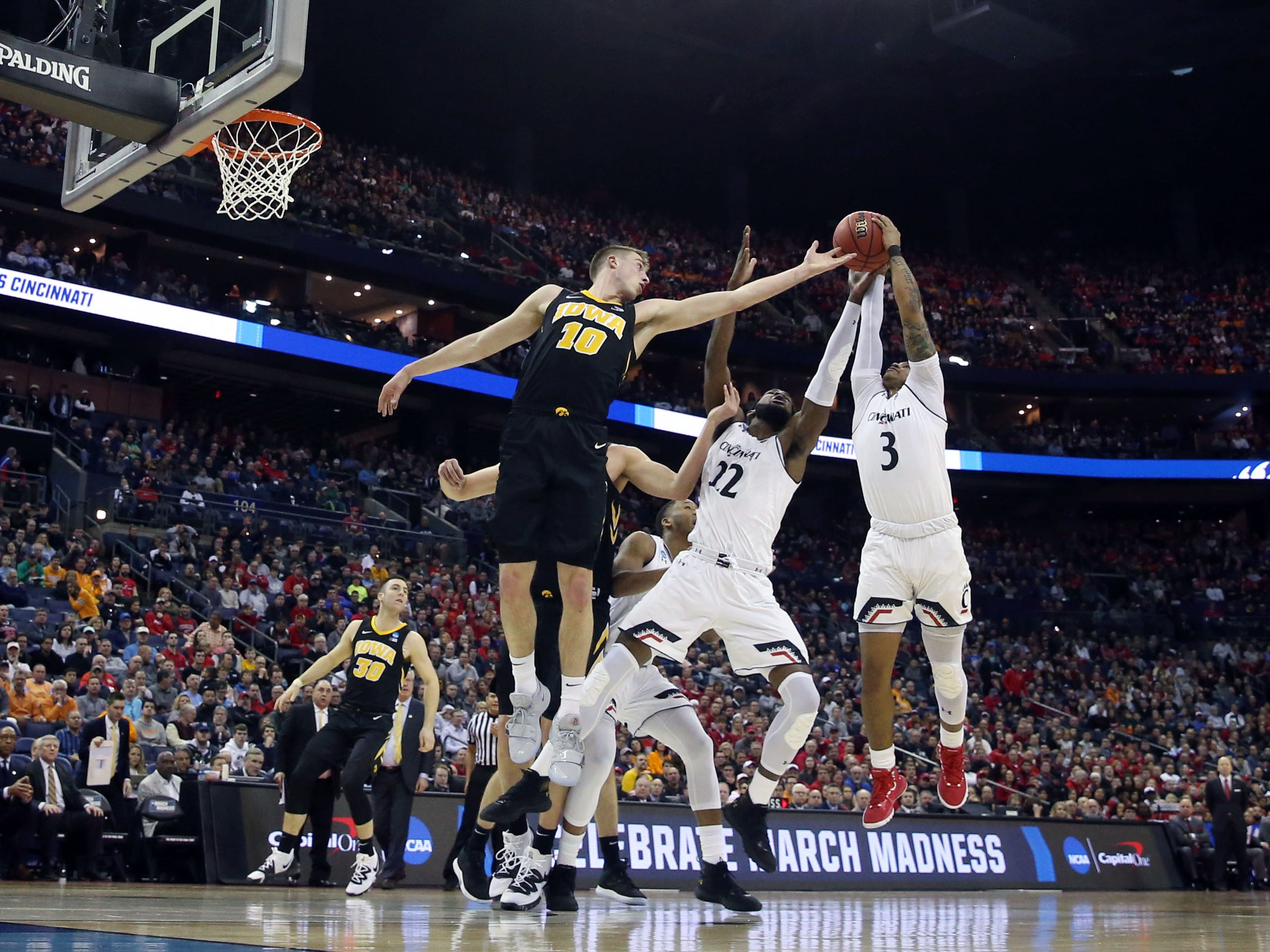 Iowa Hawkeyes guard Joe Wieskamp (10) battles for the ball with Cincinnati Bearcats forward Eliel Nsoseme (22) and guard Justin Jenifer (3)  in the first round of the 2019 NCAA Tournament at Nationwide Arena on March 22, 2019.
