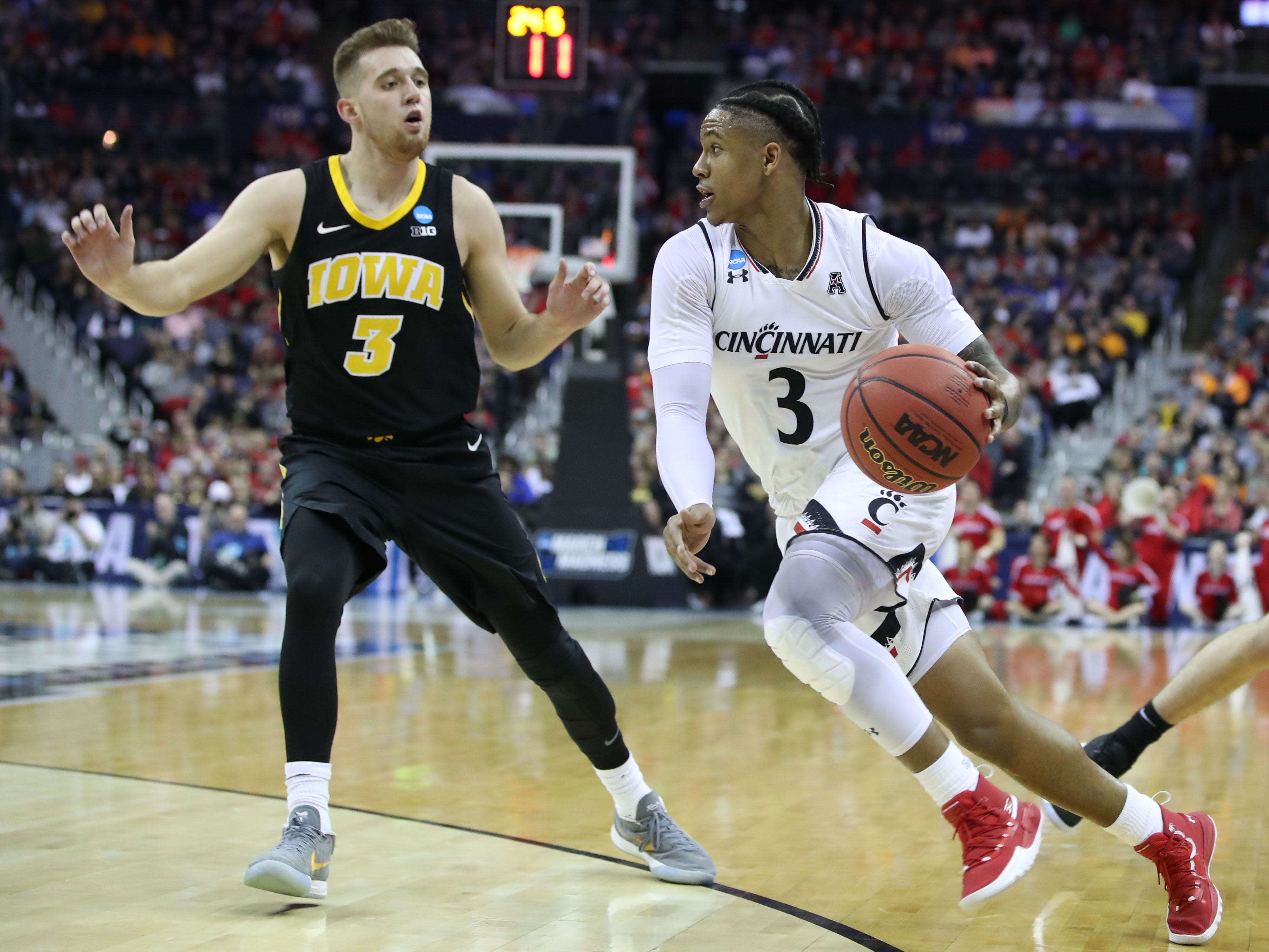 Cincinnati Bearcats guard Justin Jenifer (3) drives down the court defended by Iowa Hawkeyes guard Jordan Bohannon (3) in the first half in the first round of the 2019 NCAA Tournament at Nationwide Arena on March 22, 2019.