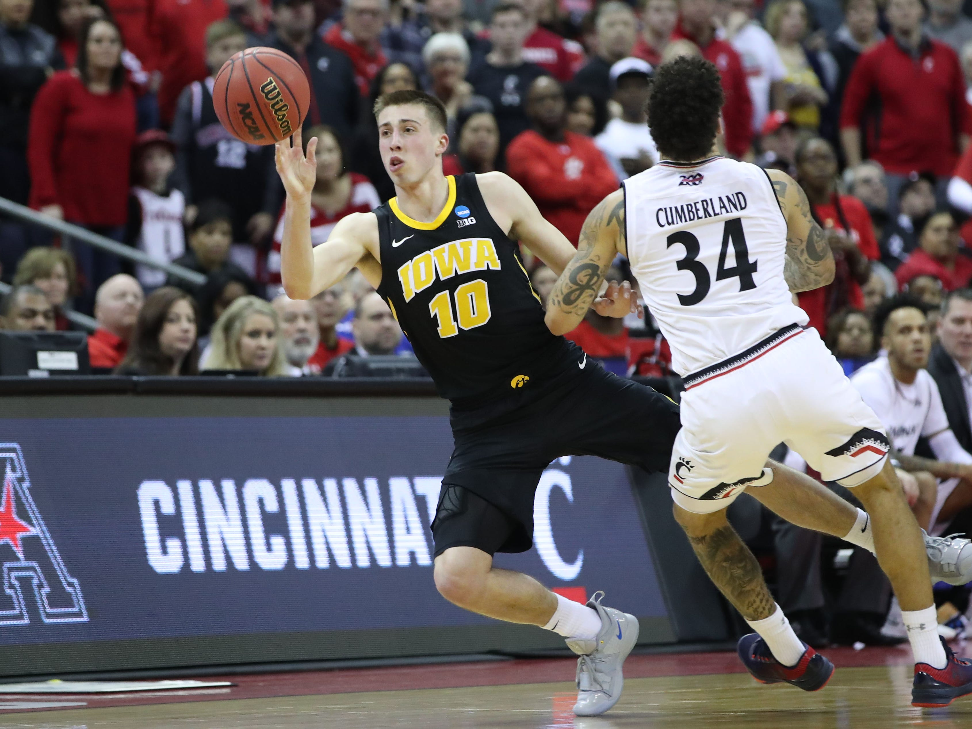 Iowa Hawkeyes guard Joe Wieskamp (10) passes the ball while falling to the court  defended by Cincinnati Bearcats guard Jarron Cumberland (34) in the second half in the first round of the 2019 NCAA Tournament at Nationwide Arena on March 22, 2019.