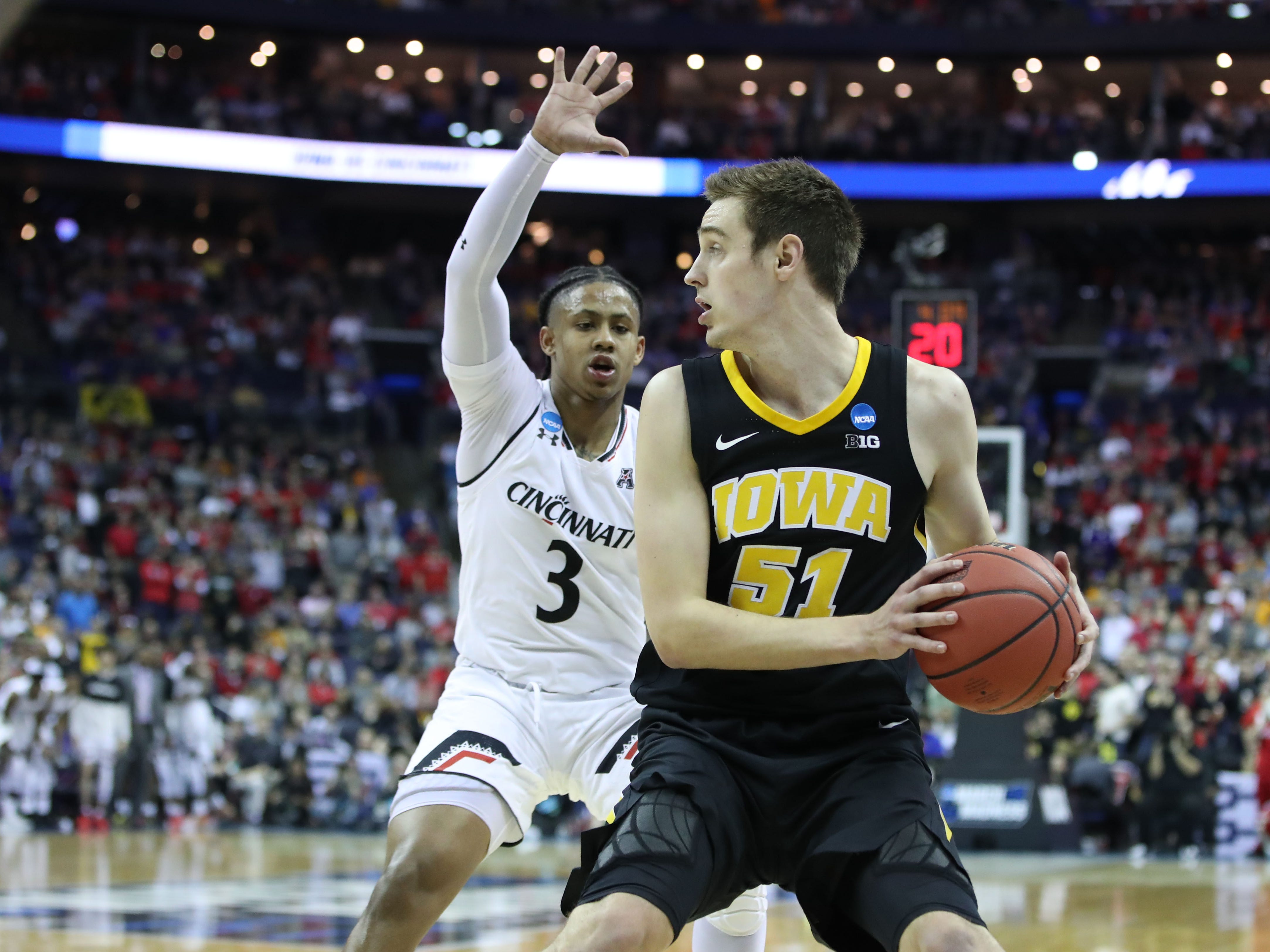 Iowa Hawkeyes forward Nicholas Baer (51) looks to move the ball defended by Cincinnati Bearcats guard Justin Jenifer (3) in the second half in the first round of the 2019 NCAA Tournament at Nationwide Arena on March 22, 2019.