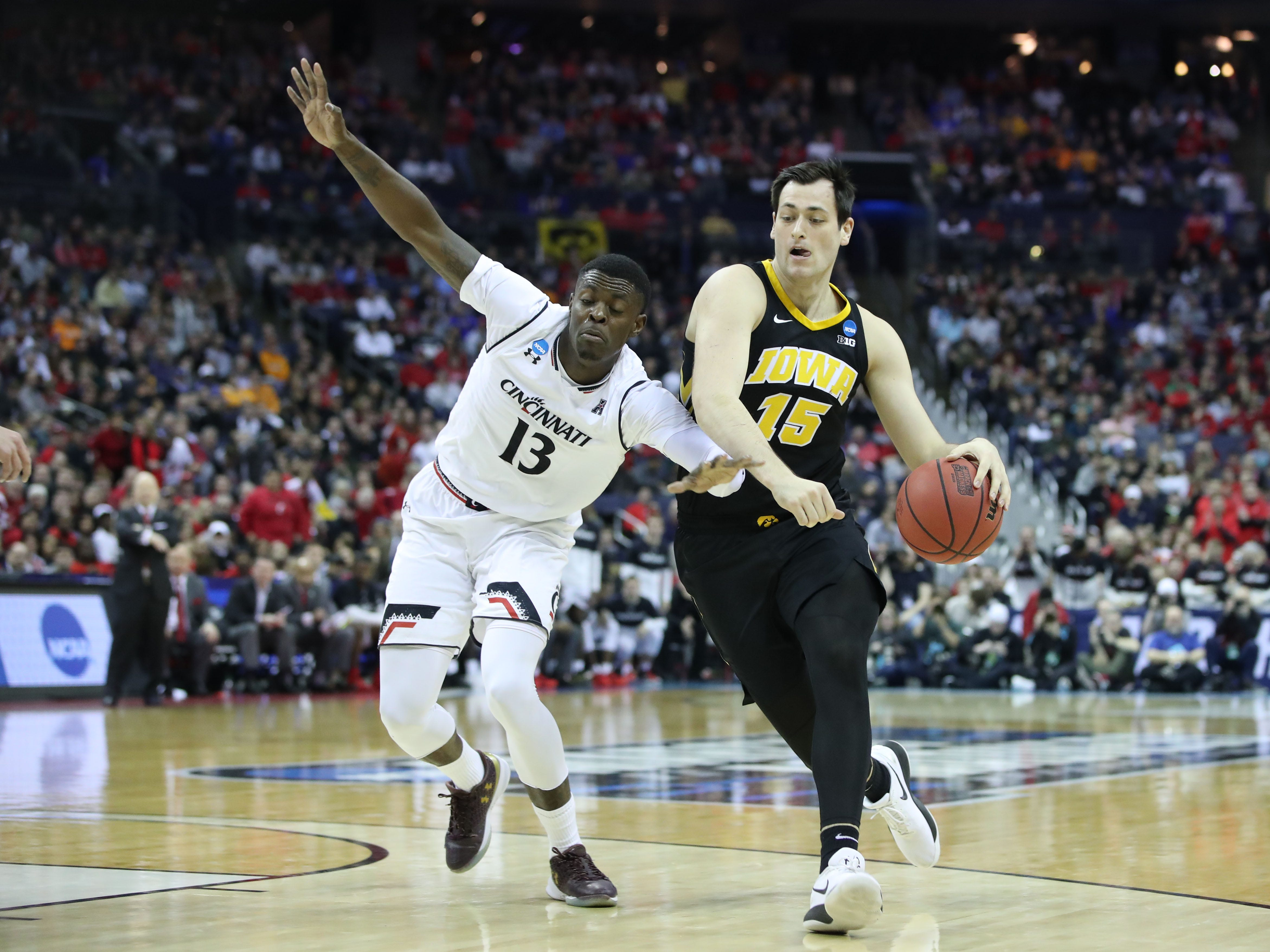Iowa Hawkeyes forward Ryan Kriener (15) dribbles down the court defended by Cincinnati Bearcats forward Tre Scott (13) in the second half in the first round of the 2019 NCAA Tournament at Nationwide Arena on March 22, 2019.