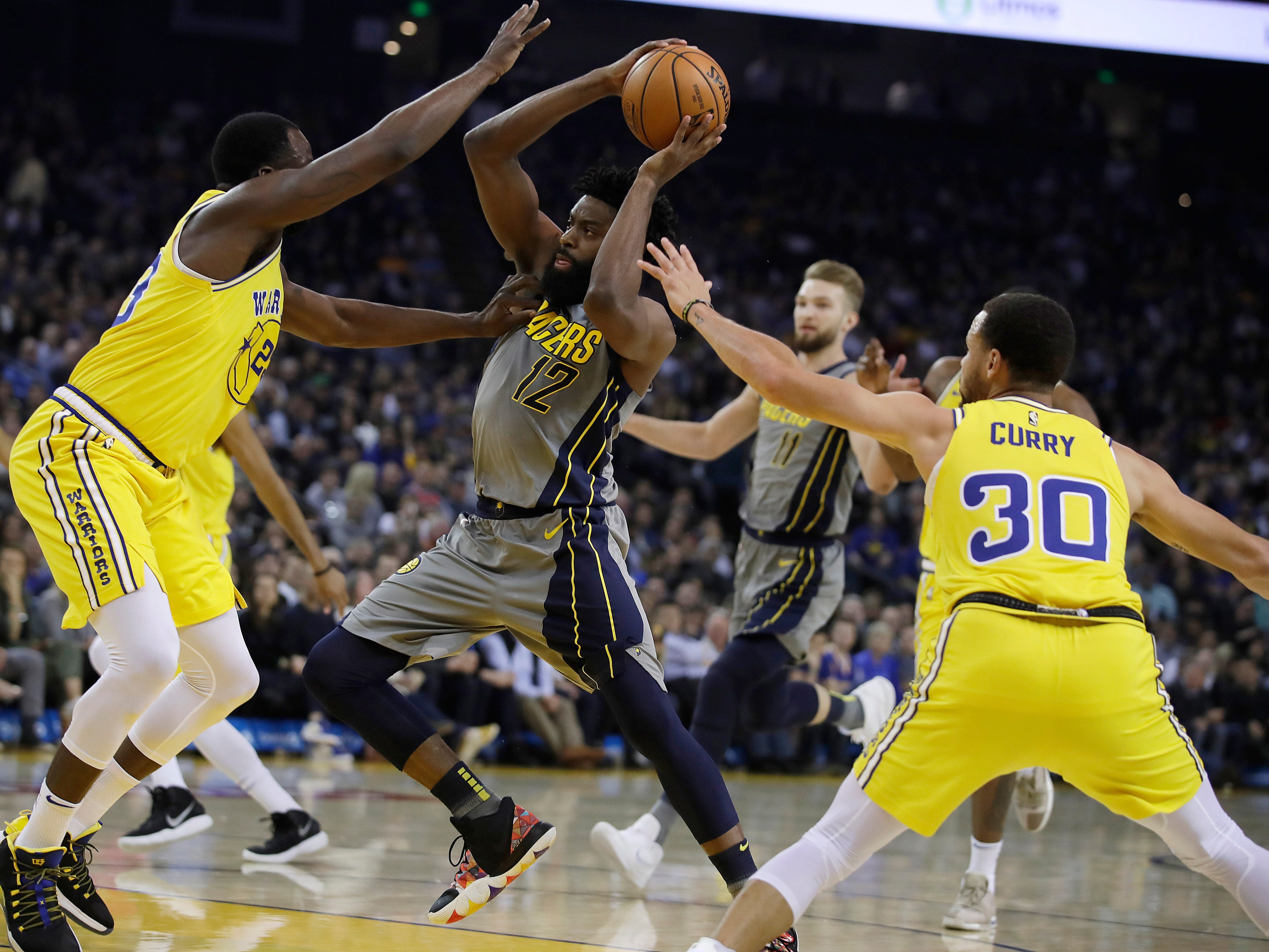 Indiana Pacers' Tyreke Evans, center, drives the ball between Golden State Warriors' Draymond Green, left, and Stephen Curry (30) during the first half of an NBA basketball game Thursday, March 21, 2019, in Oakland, Calif.
