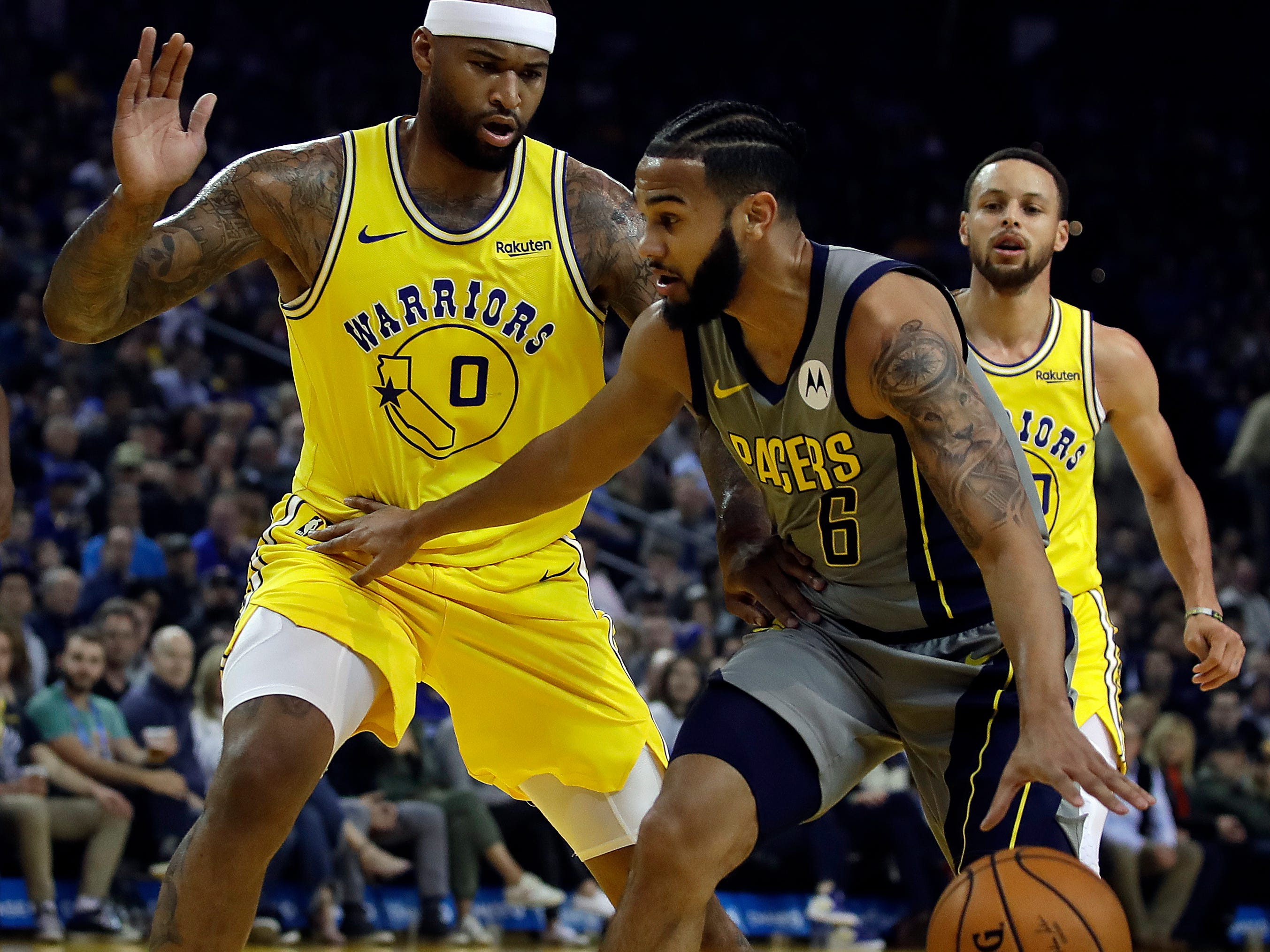 Indiana Pacers' Cory Joseph, right, drives the ball as Golden State Warriors' DeMarcus Cousins (0) defends during the first half of an NBA basketball game Thursday, March 21, 2019, in Oakland, Calif.