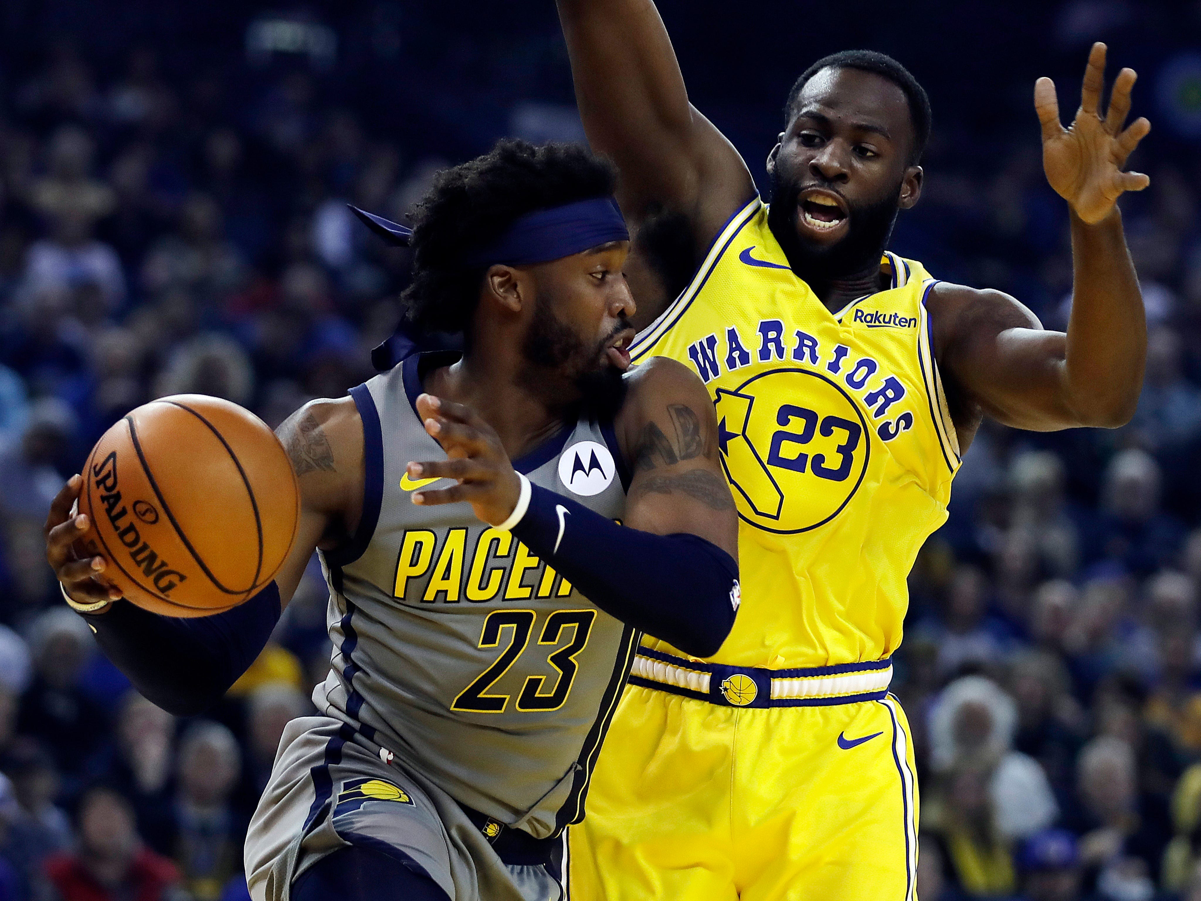 Indiana Pacers' Wesley Matthews, left, looks to pass the ball as Golden State Warriors' Draymond Green defends during the first half of an NBA basketball game Thursday, March 21, 2019, in Oakland, Calif.