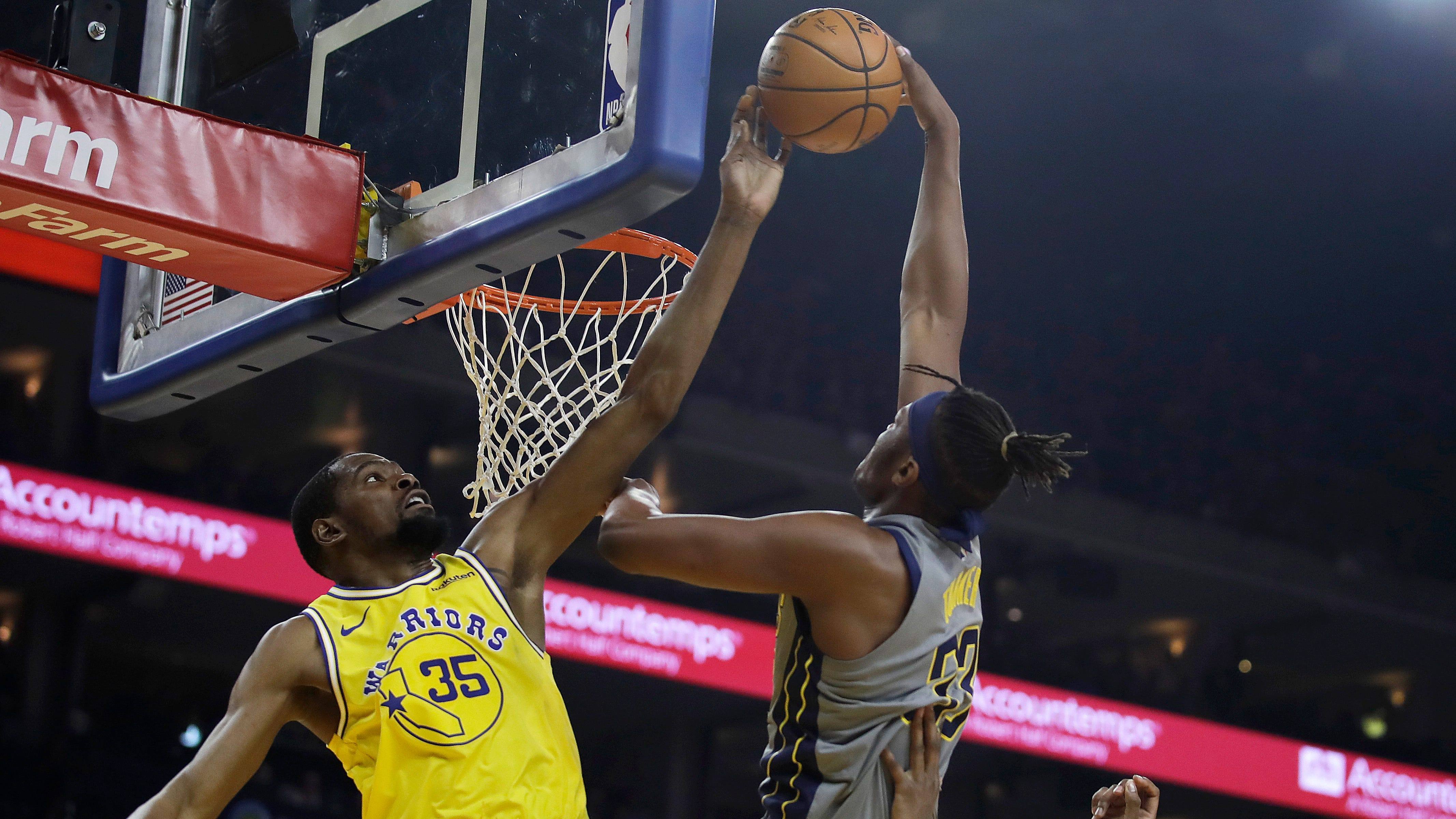 Golden State Warriors' Kevin Durant, left, blocks a shot from Indiana Pacers' Myles Turner (33) during the first half of an NBA basketball game Thursday, March 21, 2019, in Oakland, Calif.