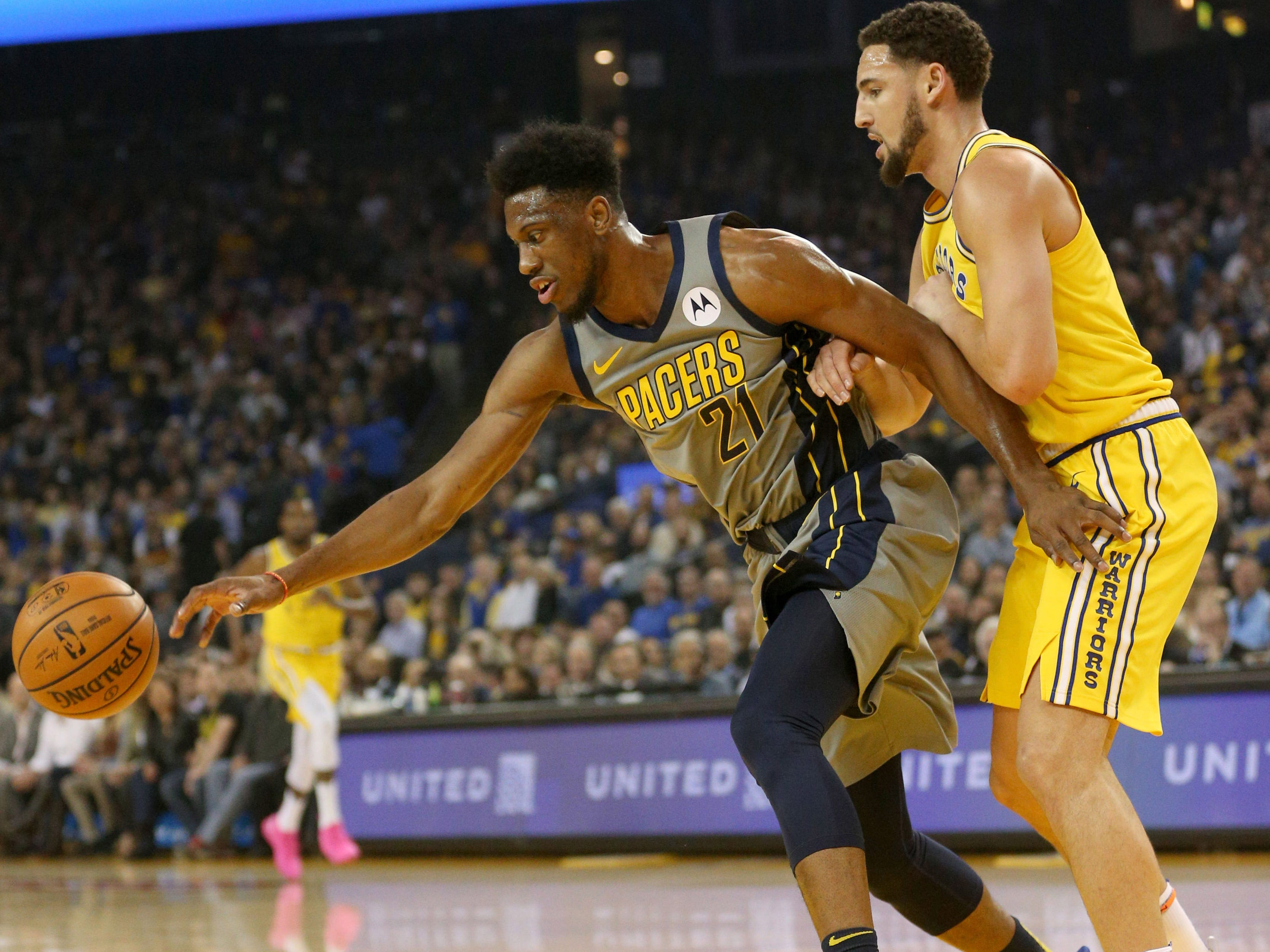 Mar 21, 2019; Oakland, CA, USA; Indiana Pacers forward Thaddeus Young (21) attempts to gain control of the ball next to Golden State Warriors guard Klay Thompson (11) in the first quarter at Oracle Arena.
