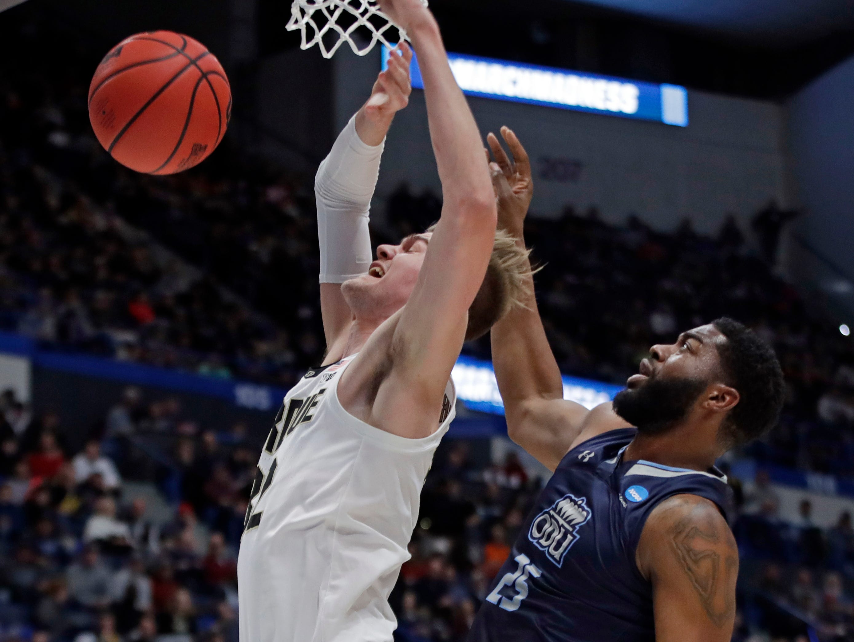 Purdue's Matt Haarms, left, is fouled as he goes to the hoop by Old Dominion's Elbert Robinson III (25) during the first half of a first round men's college basketball game in the NCAA Tournament, Thursday, March 21, 2019, in Hartford, Conn.